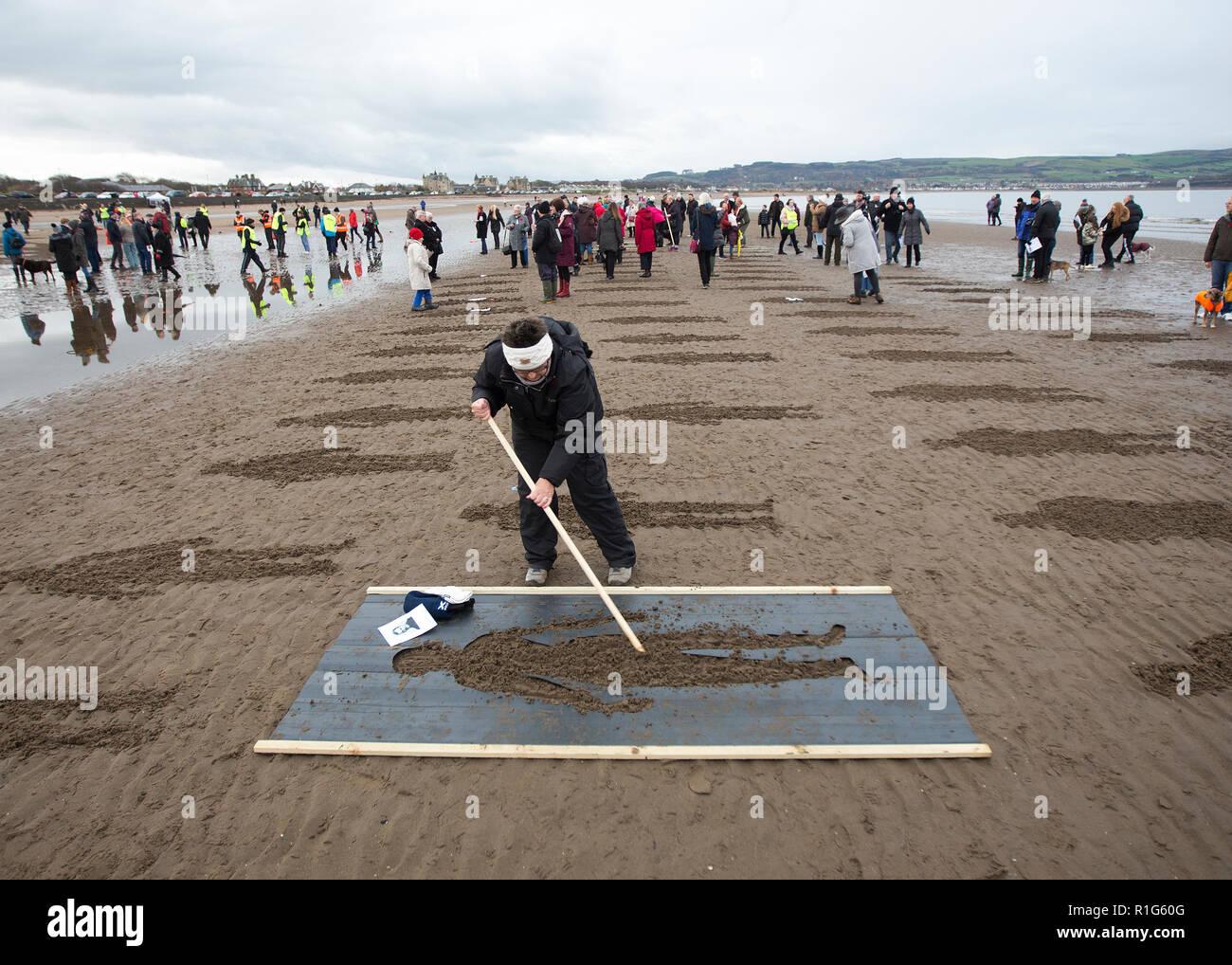 Personnes créant des pochoirs de soldat dans le sable pour Danny Boyle's WW1 Pages 'à la mer' projet sur plage d'Ayr Ayrshire, Ecosse en Banque D'Images