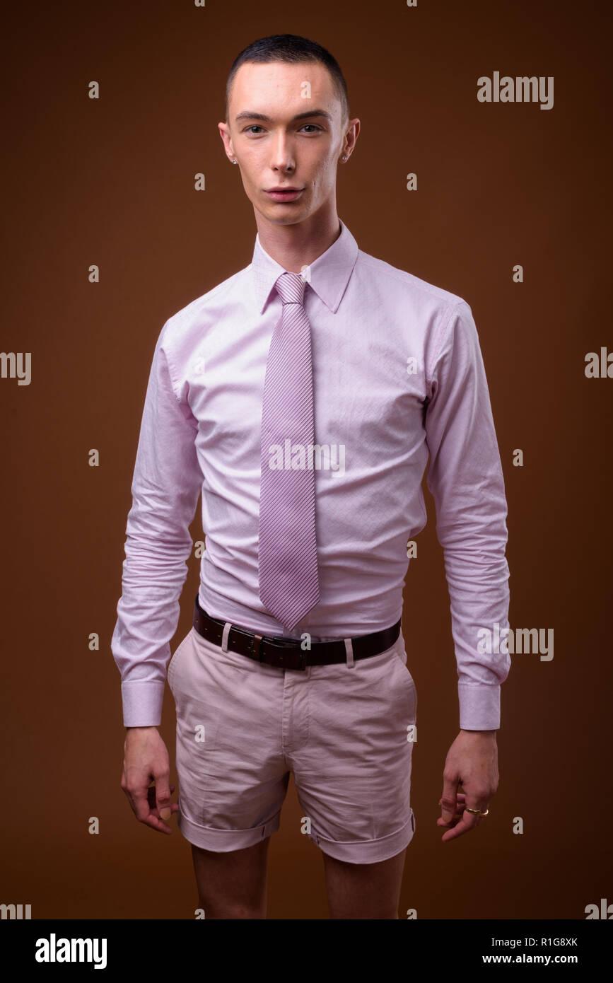 Beau Jeune Homme beau jeune homme androgyne contre fond brun banque d'images, photo