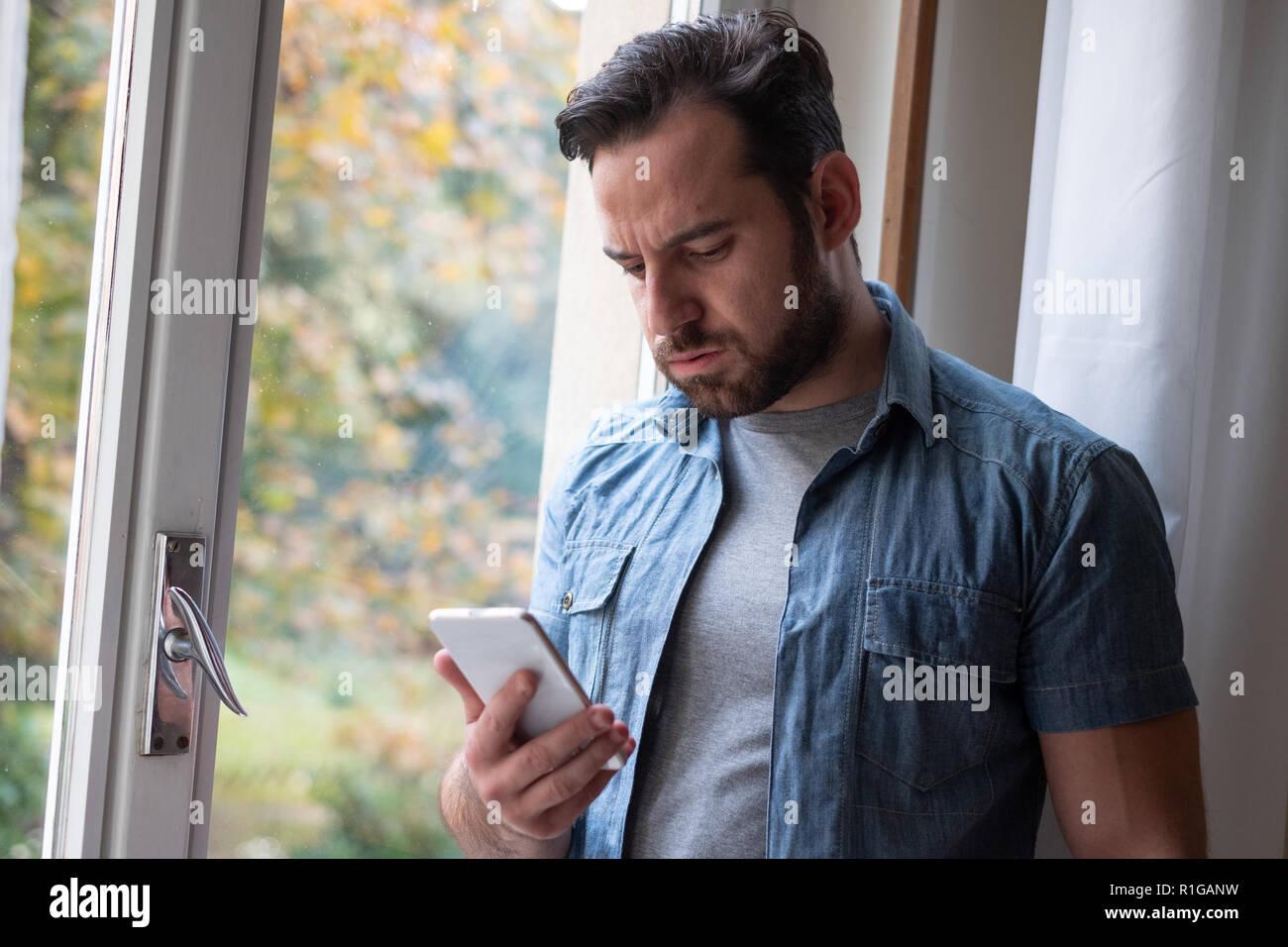 L'homme inquiet regardant smartphone et message d'attente Photo Stock