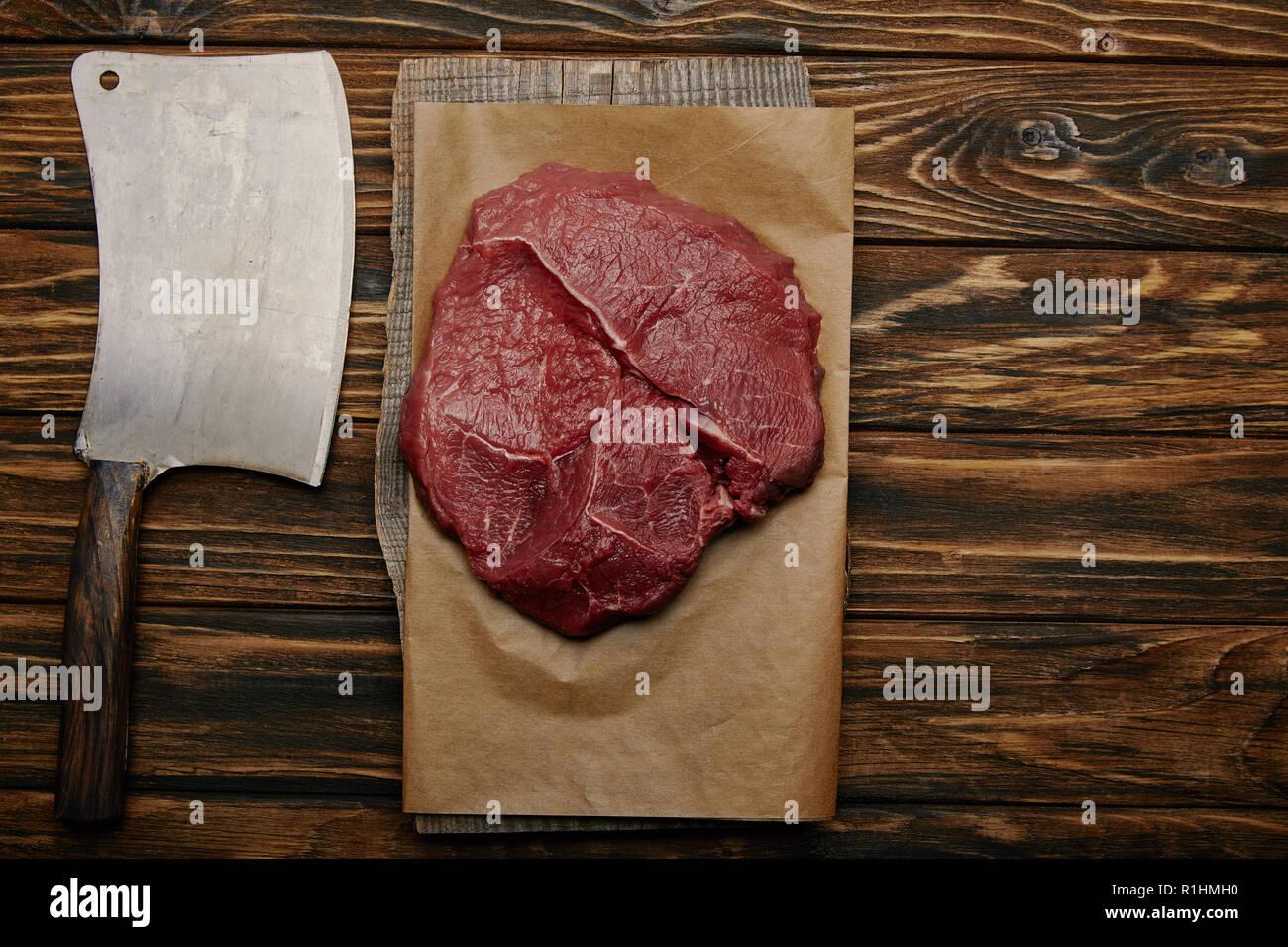 Vue de dessus de la viande crue sur du papier sulfurisé avec couteau de boucher sur fond de bois Photo Stock