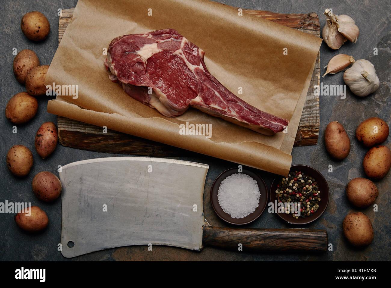 Mise à plat avec des faux-filet bifteck sur le papier cuisson avec couteau de boucherie, épices, pommes de terre et l'ail Photo Stock