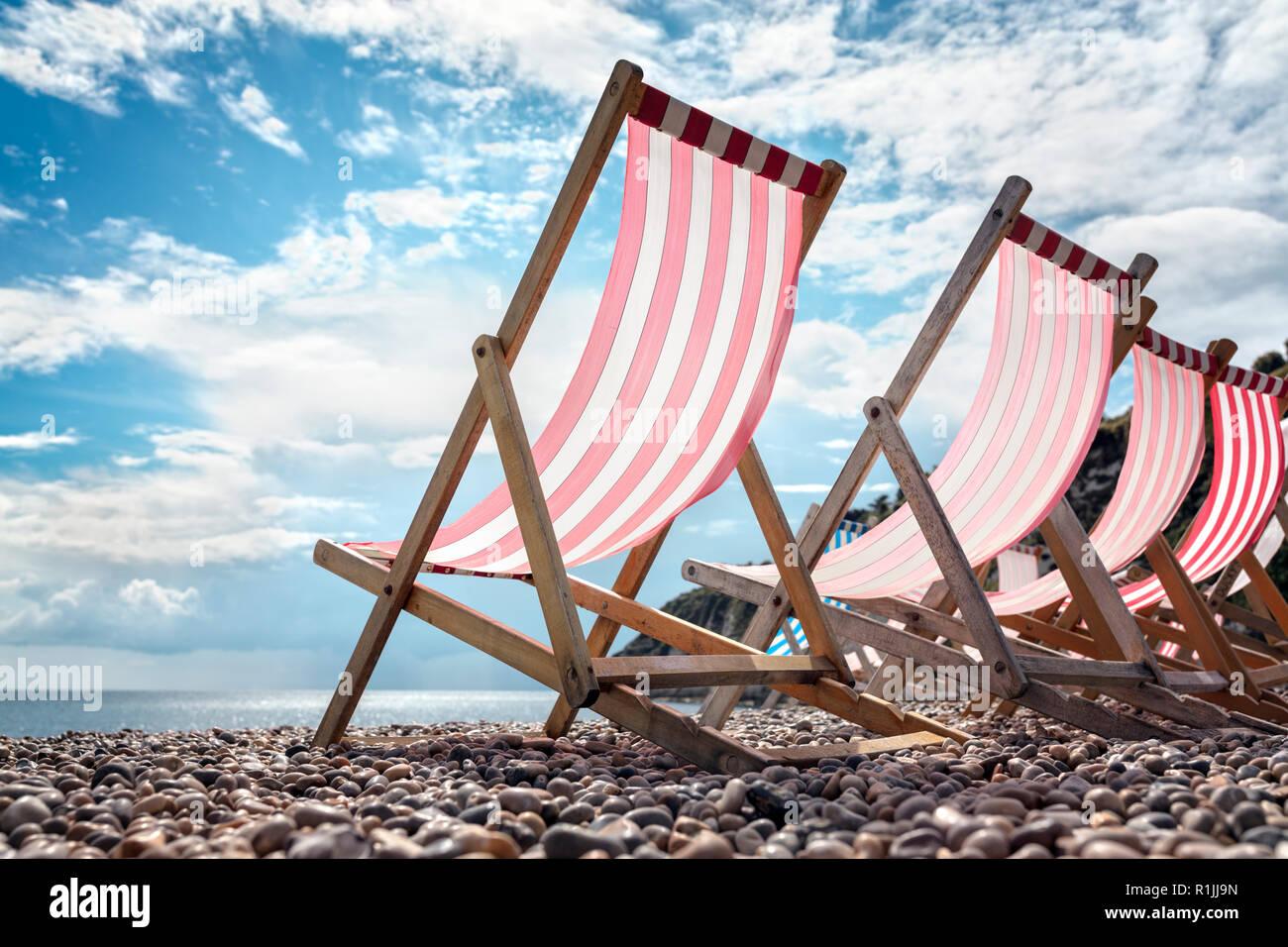 Transats sur la plage au bord de la mer, sur les vacances d'été Banque D'Images