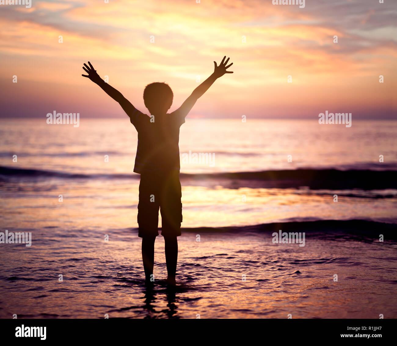 Silhouette d'un garçon avec les mains posées dans le coucher de soleil sur la mer concept pour la religion, le culte, la prière et la louange Banque D'Images