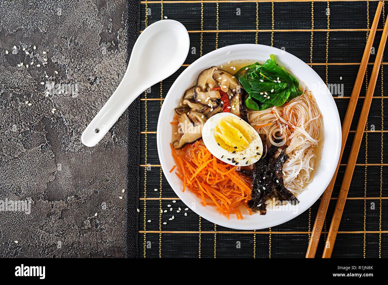 Végétarien régime bol de soupe de nouilles de champignons shiitake, carottes et œufs durs. La nourriture japonaise. Vue d'en haut. Mise à plat Photo Stock