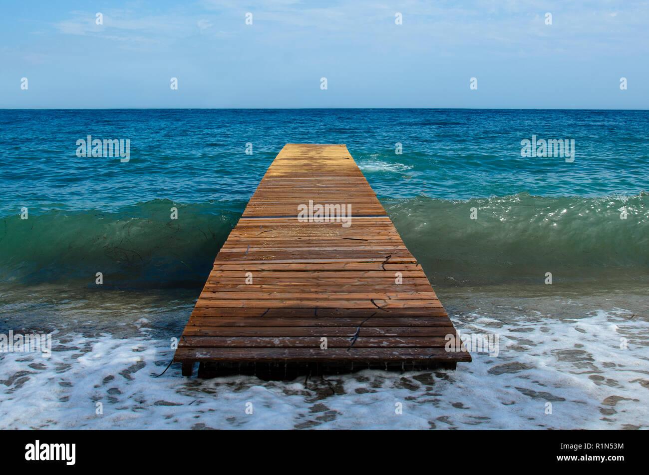 Jetée en bois sur la mer infinie sans que personne, il passe sous une vague qui se brise sur la rive Photo Stock