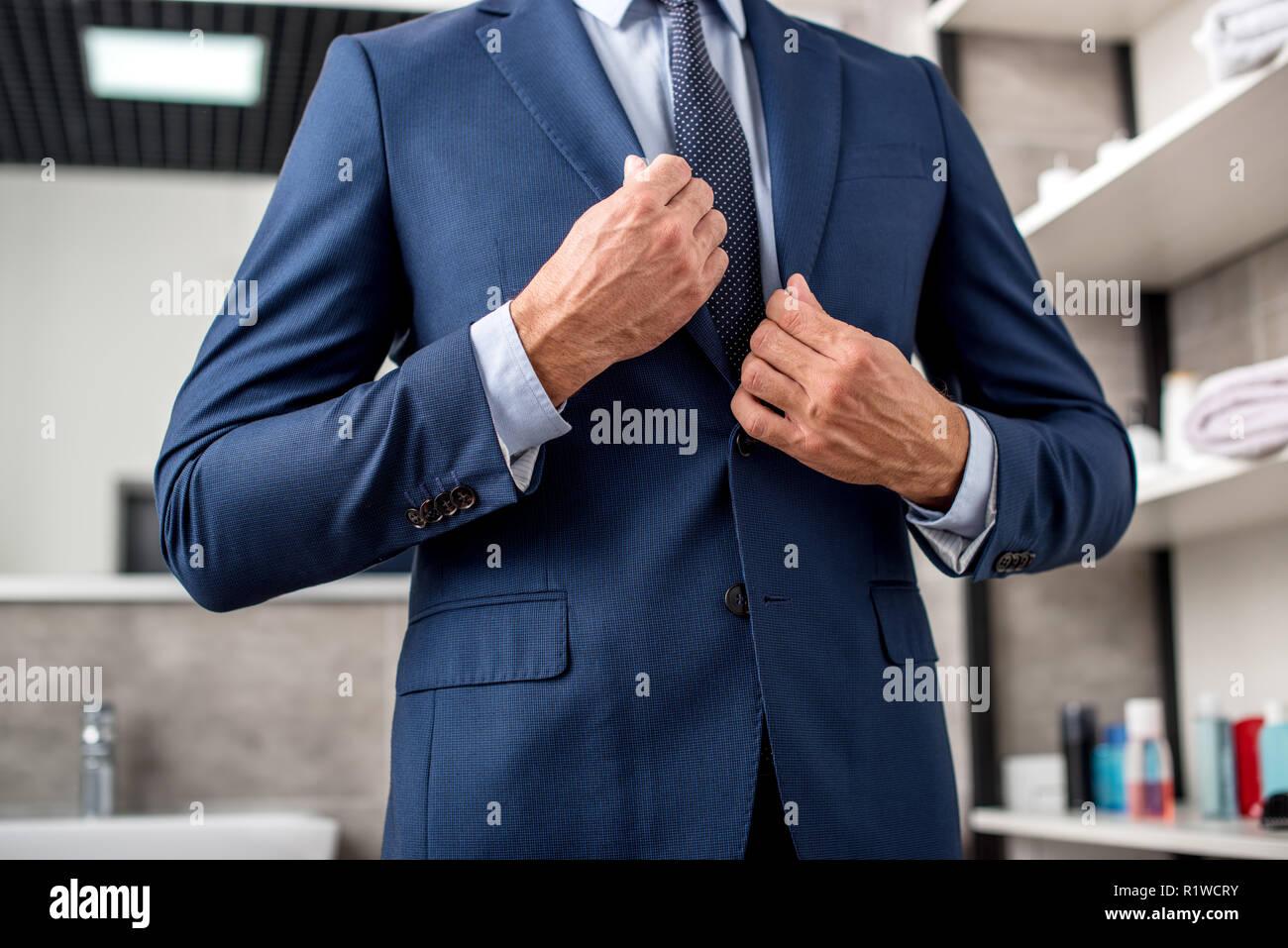 Cropped shot of businessman adjusting veste de costume dans la salle de bains Banque D'Images