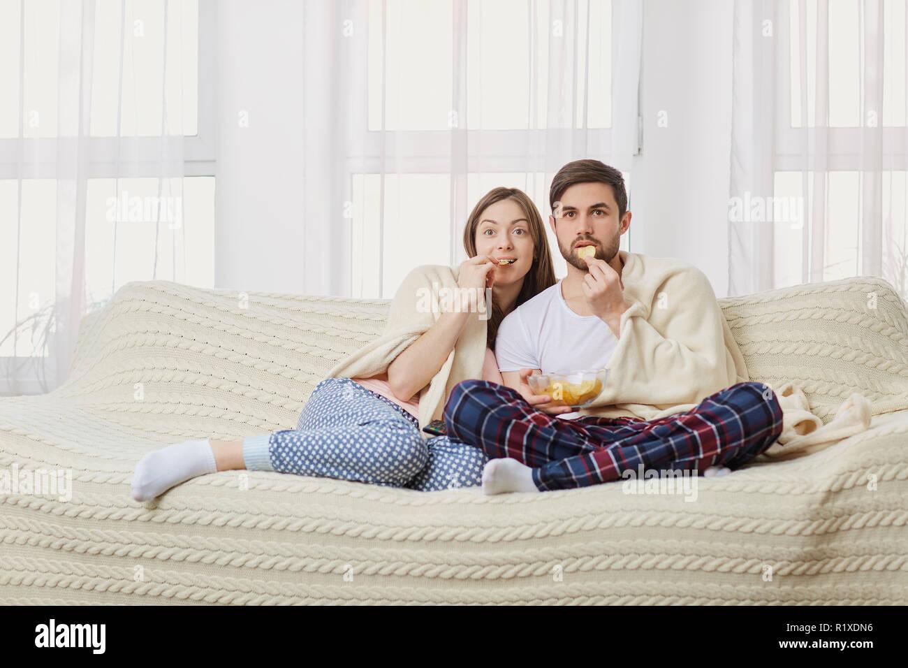 Un jeune couple assis sur le canapé à regarder un plat intéressant . Photo Stock
