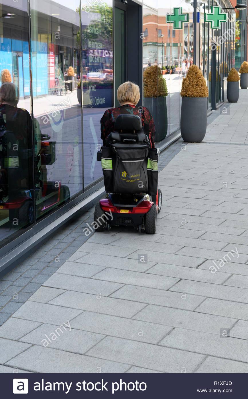 Femme à l'aide de mobility scooter, le Centre Orchard, Didcot, Berkshire, England, UK Photo Stock