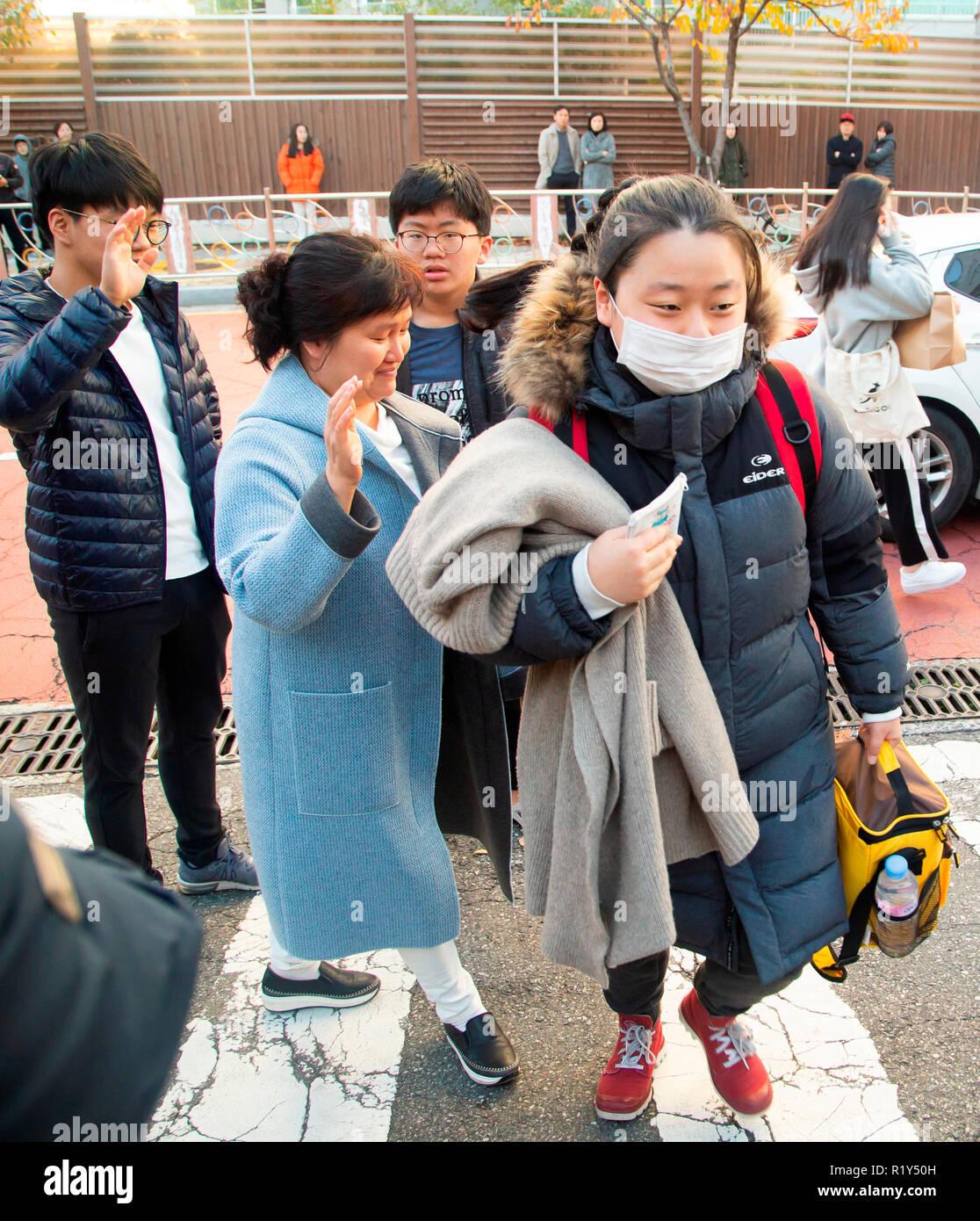 Busan, Séoul, Corée du Sud. 15 Nov 2018. Une mère (2e L) encourage sa fille (R), un lycéen comme les jeunes frères voir son arrêt en face d'une salle d'examen de l'examen d'entrée à l'université nationale de Pusan, environ 420 km (261 milles) au sud-est de Séoul, Corée du Sud. La Corée du Sud a tenu l'examen d'entrée à l'université annuelle nationale, le Collège Scholastic Aptitude Test (CSAT) le jeudi et environ 540 000 candidats ont passé l'examen pour cette année. Credit: Lee Jae-Won/AFLO/Alamy Live News Photo Stock