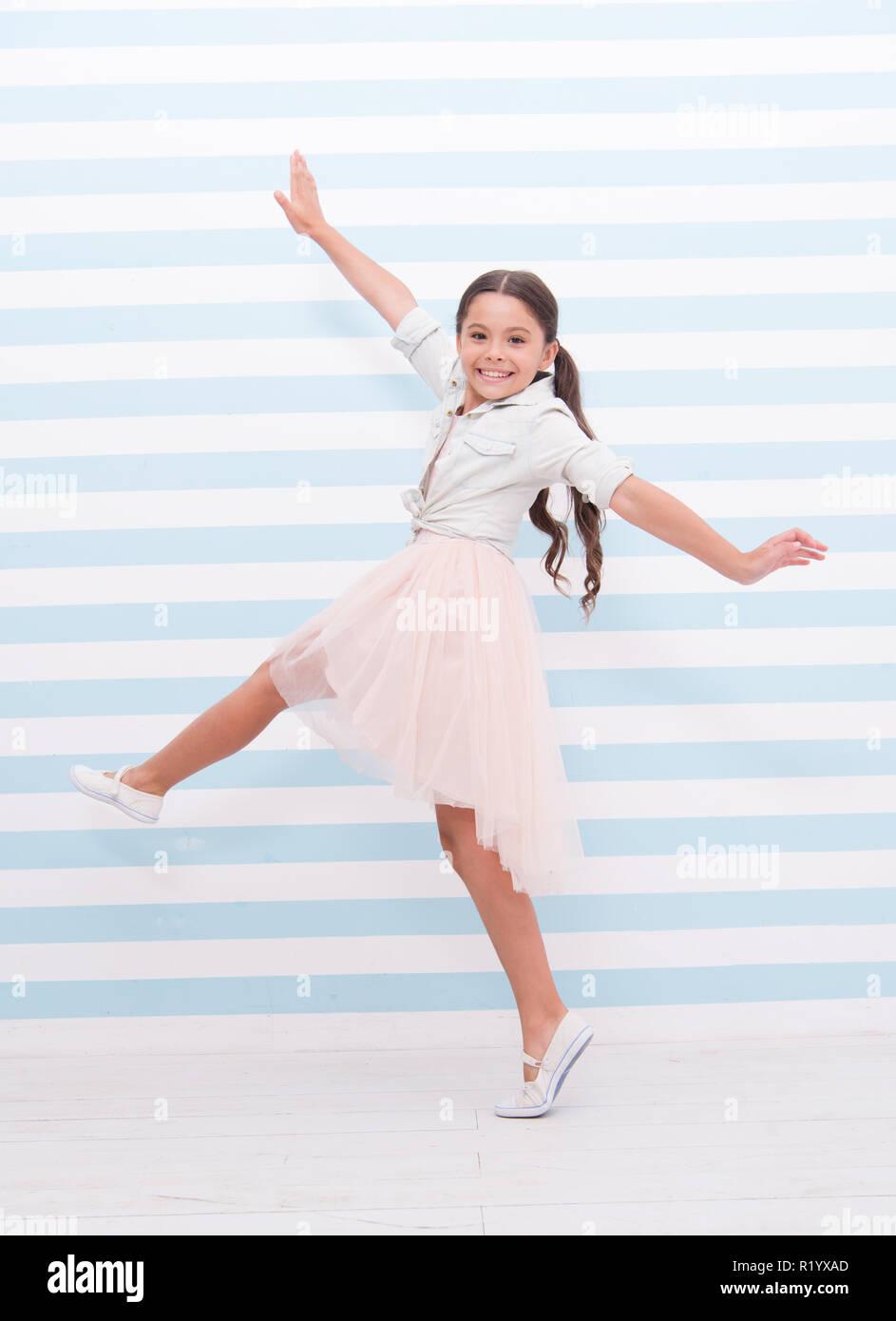 Concept de l'enfant. Heureux petit enfant de la danse. Fille enfant sourire dans la mode vestimentaire. Enfant et l'enfance. sens de la liberté. Photo Stock
