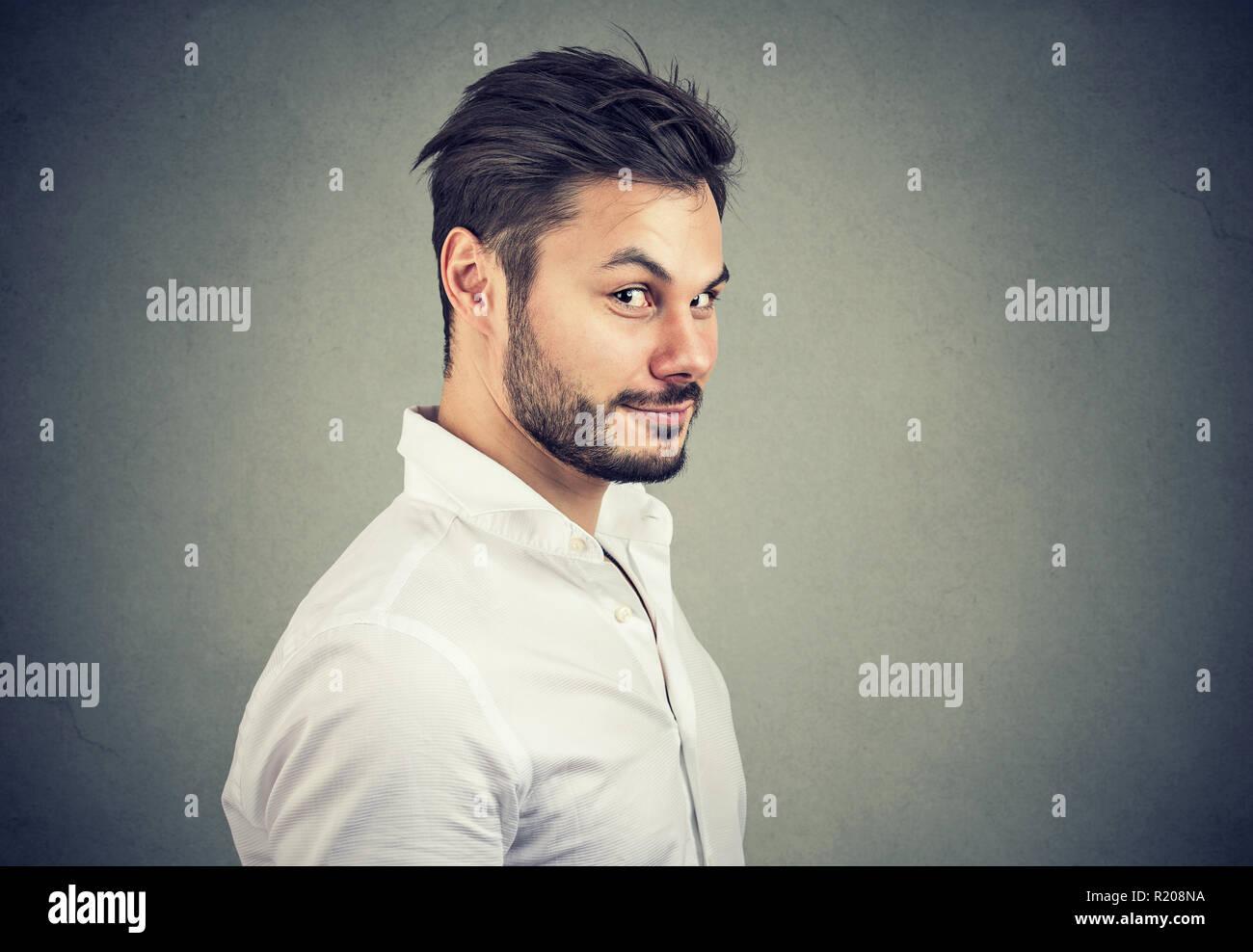 Jeune homme malhonnête en chemise blanche à prétendre avec sourire à huis clos sur fond gris Photo Stock