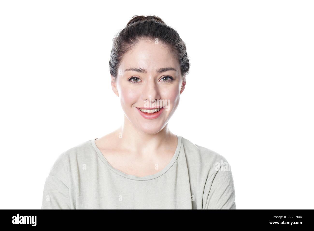 Jeune femme gaie dans son 20s avec le maquillage naturel et des cheveux bun smiling brunette - isolé sur fond blanc Photo Stock