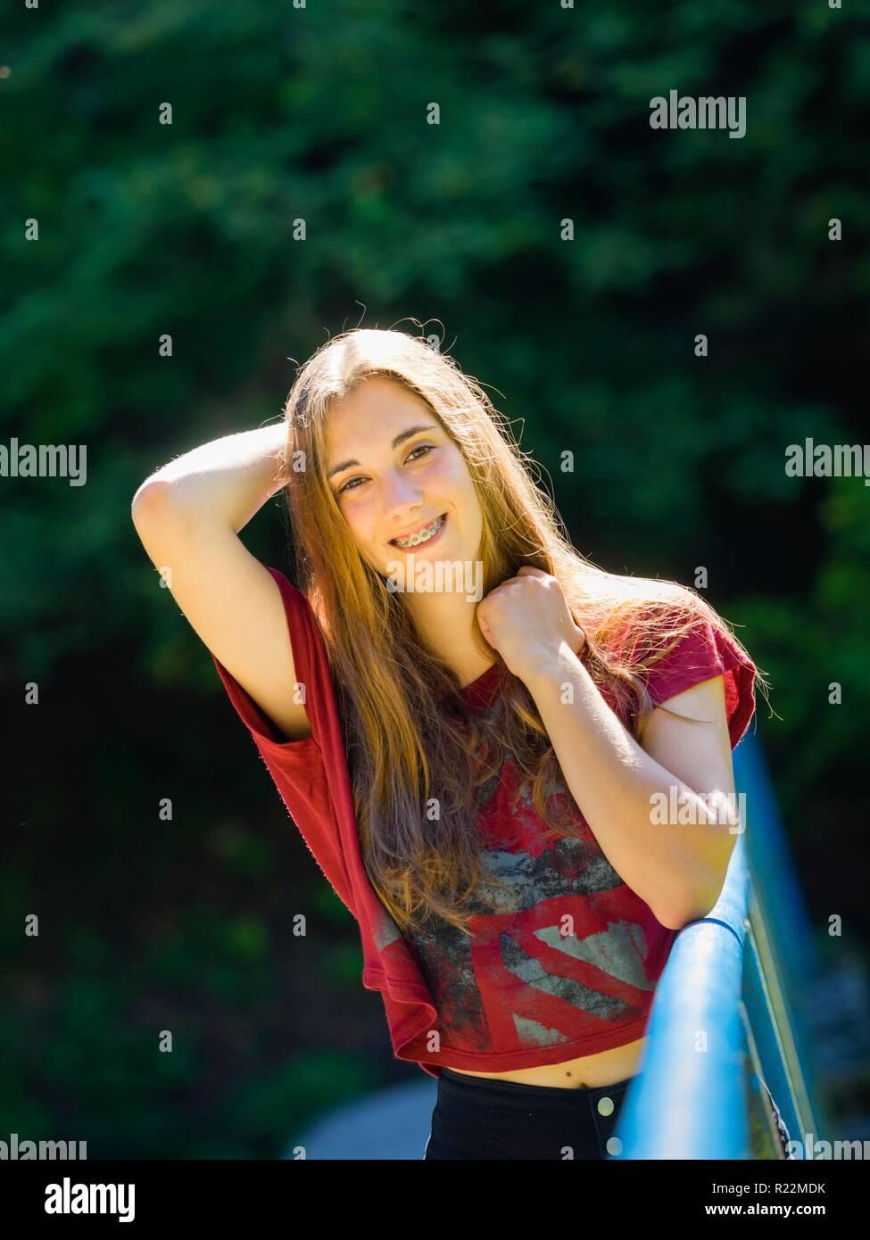 Les renforts des dents young teen femme yeux-contact smiling at camera Banque D'Images