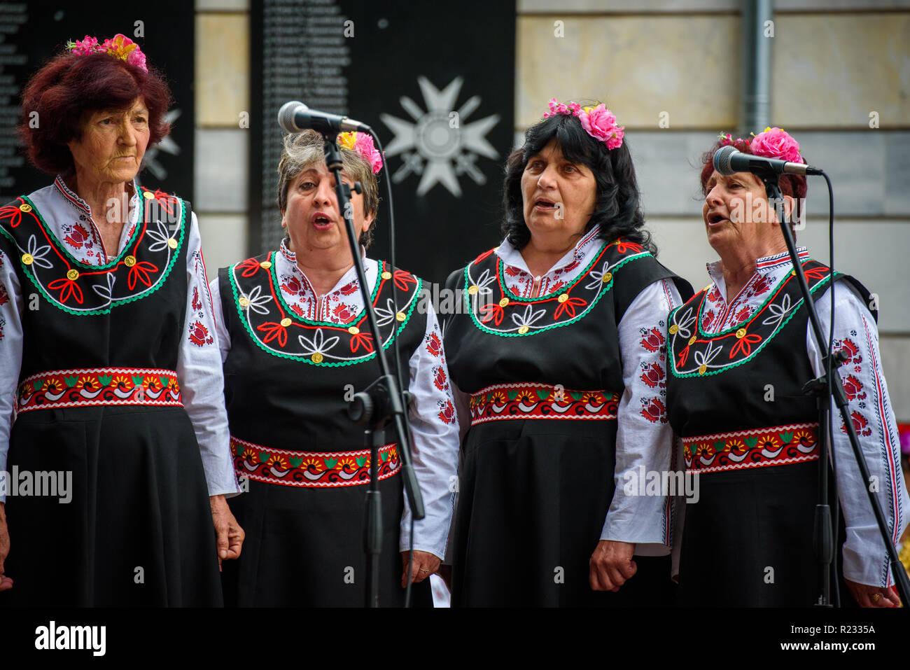 Groupe de femmes en costumes folkloriques bulgares traditionnels - chanter  une chanson à un festival de 31d5b93825f
