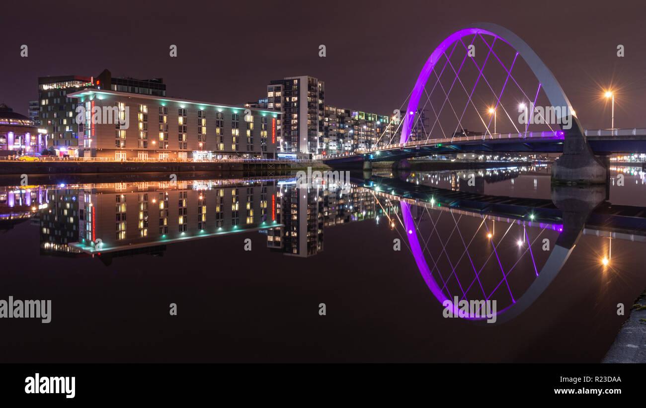 Glasgow, Scotland, UK - 4 novembre, 2018: immeubles modernes se reflètent dans la rivière Clyde à côté de la Clyde Arc à Glasgow dans la nuit. Banque D'Images