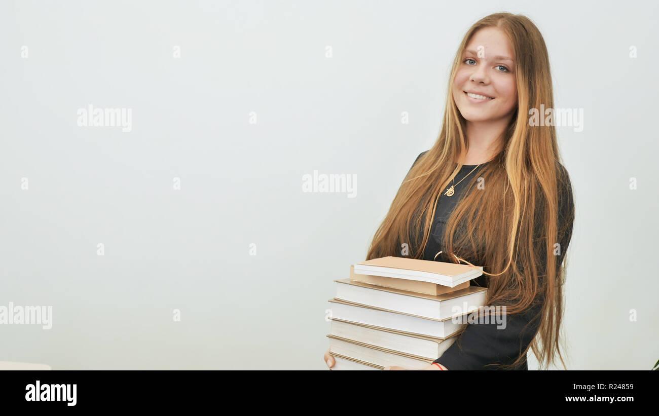 Une écolière de bonne humeur avec une pile de livres. Photo Stock