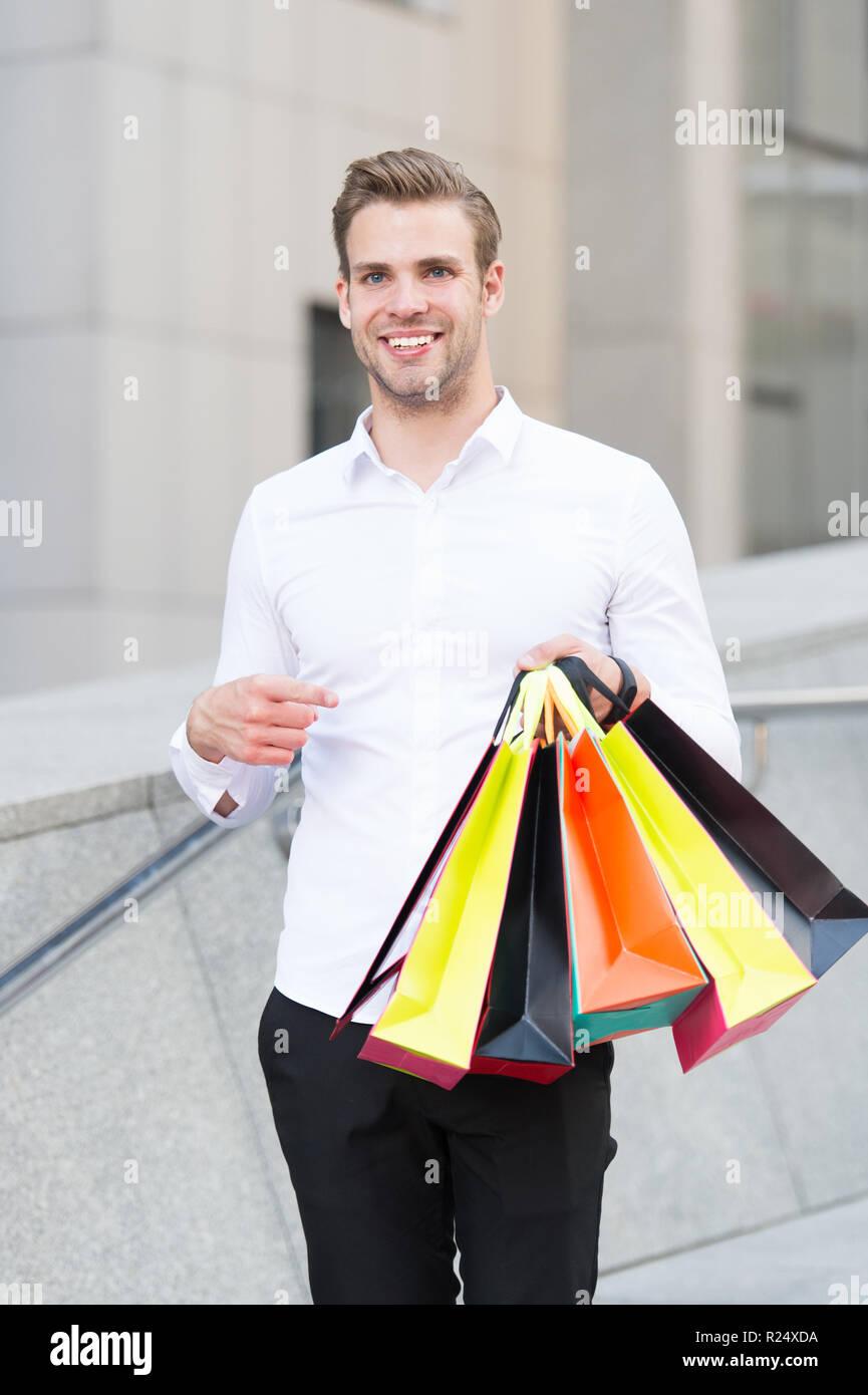 Homme Vêtements officiels portent des sacs de magasinage. Guy heureux faire bande sacs. Des affaires. C'est sur le noir vendredi. Maintenez l'homme sacs sacs papier lot après shopping in mall. Le vendredi noir vente concept. Banque D'Images