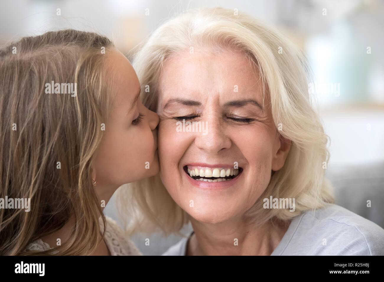 Jolie petite-fille baisers vieille grand-mère souriante sur che Photo Stock