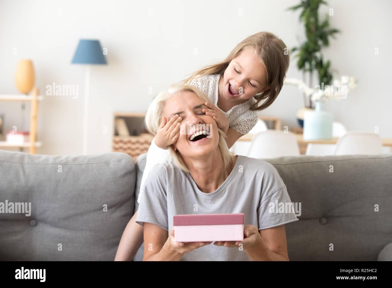 Petite-fille fermer les yeux de grand-mère holding Photo Stock