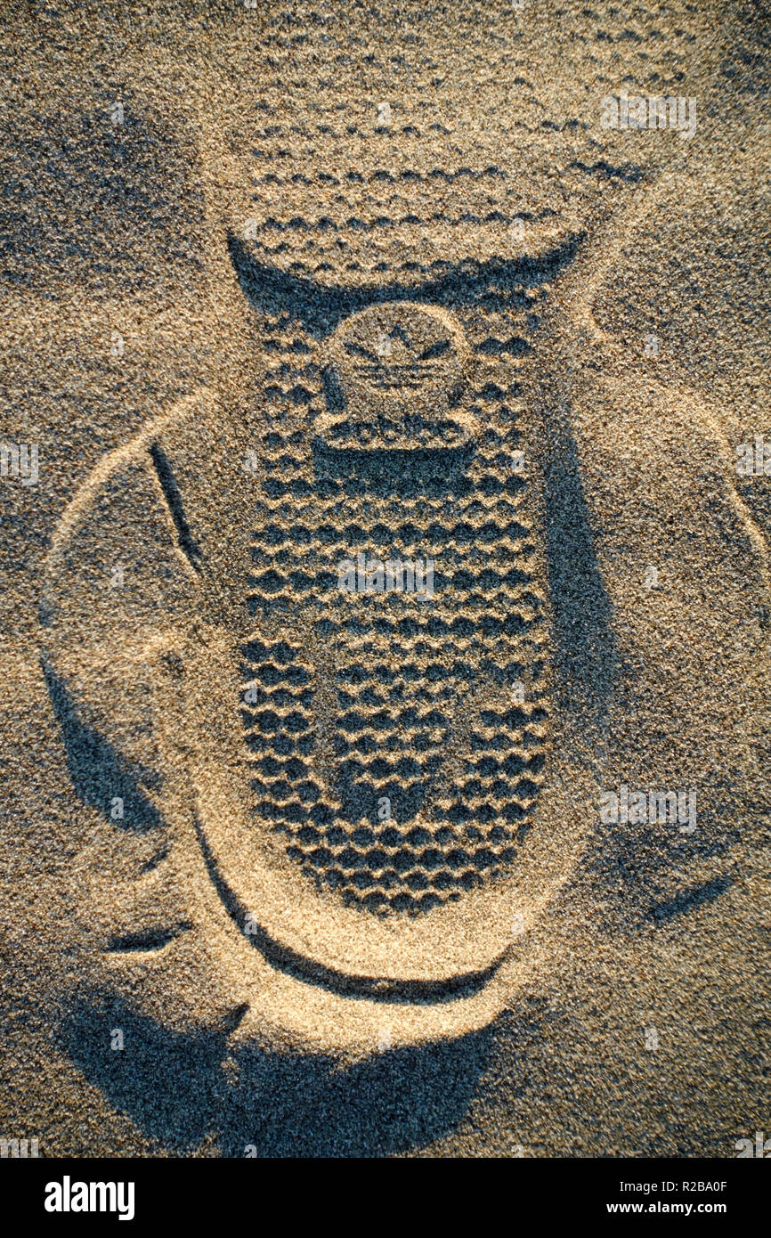 Logo de marque adidas chaussure empreinte sur le sable d'une plage ...