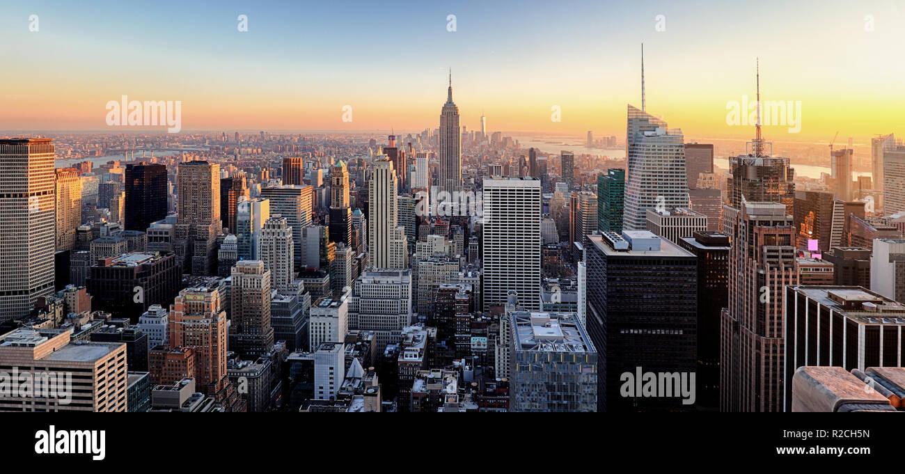 La ville de New York. Le centre-ville de Manhattan avec l'Empire State Building illuminé et gratte-ciel au coucher du soleil. Banque D'Images