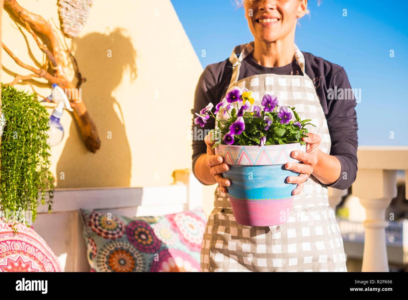 L'âge moyen Beautiful woman smiling au travail sur la terrasse avec un petit jardin. Fait à la main avec des dessins d'art mandala et pastels. La lumière du soleil et le visage coupé Banque D'Images