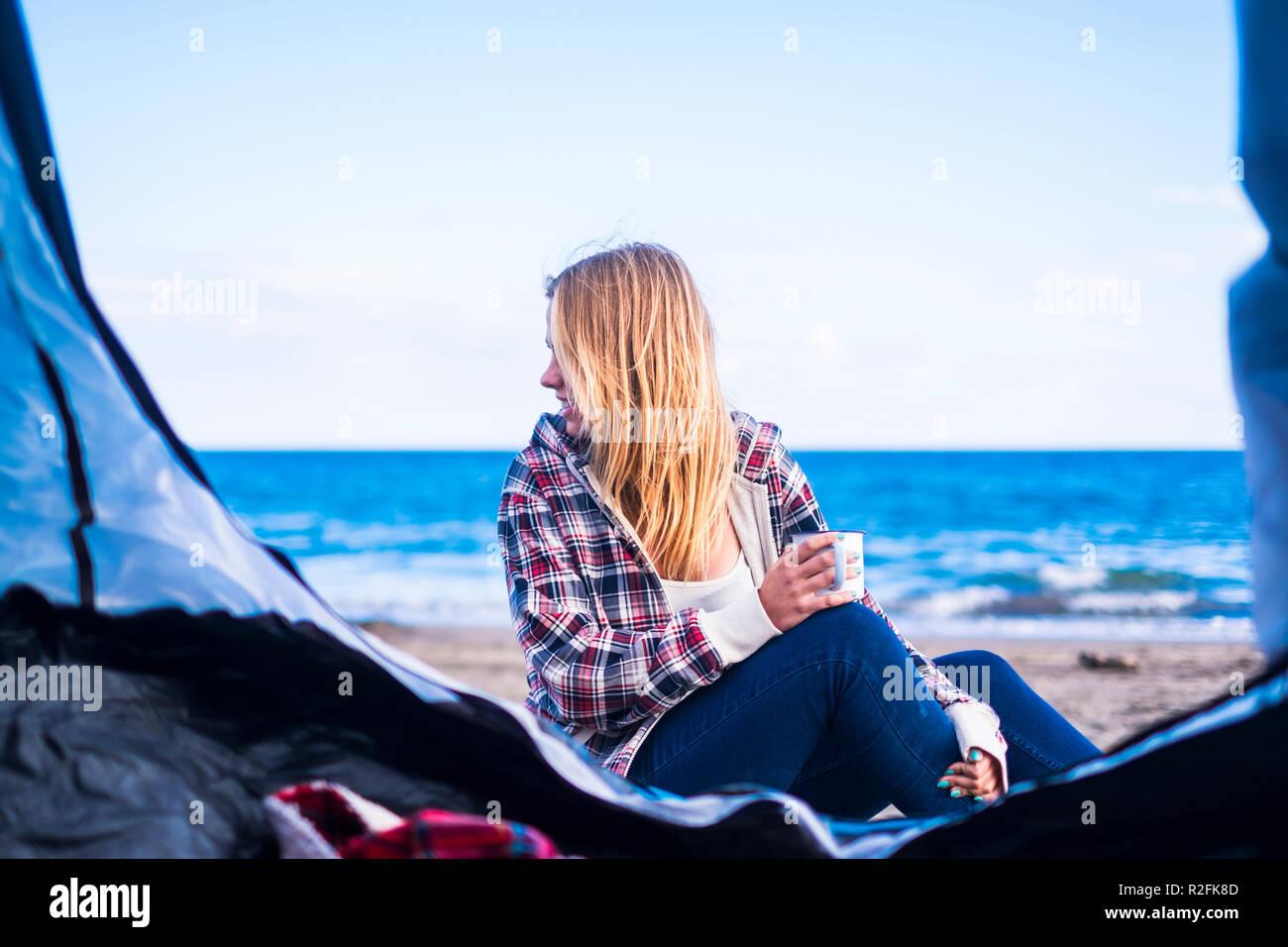 D'autres modes de vie et de vacances concept pour la fille blonde s'asseoir à la recherche à l'océan sur la porte de sa tente. Tenerife locetion. Photo Stock