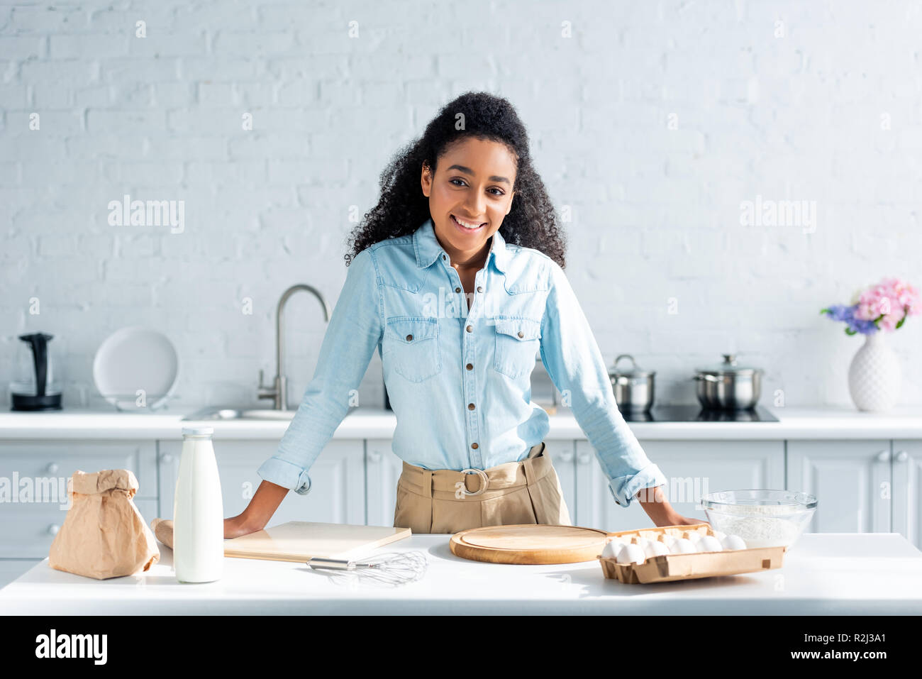 Smiling attractive african american girl leaning on kitchen counter and looking at camera Banque D'Images
