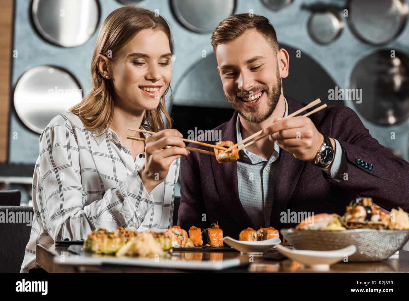 Smiling attractive young woman eating sushi ensemble dans restaurant Banque D'Images