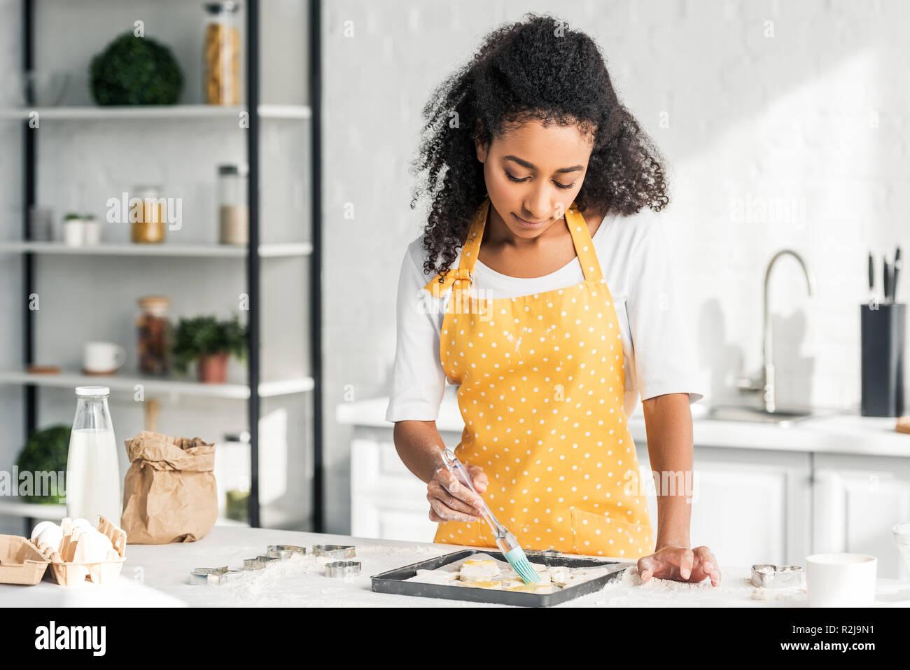 Attractive african american girl en tablier d'appliquer de l'huile sur les cookies non cuits dans la cuisine Photo Stock