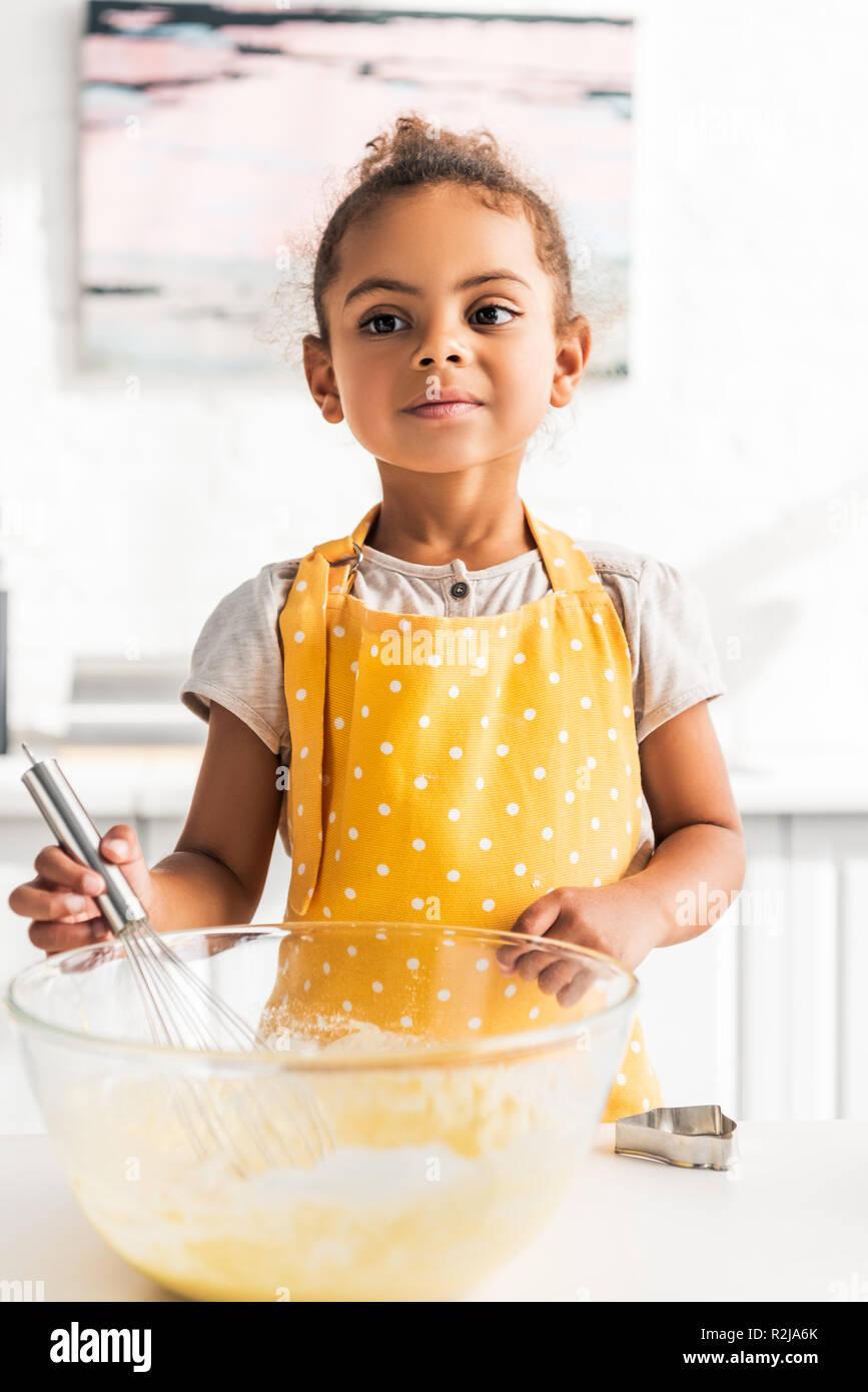 Adorable african american kid la préparation et fouetter la pâte en cuisine Photo Stock