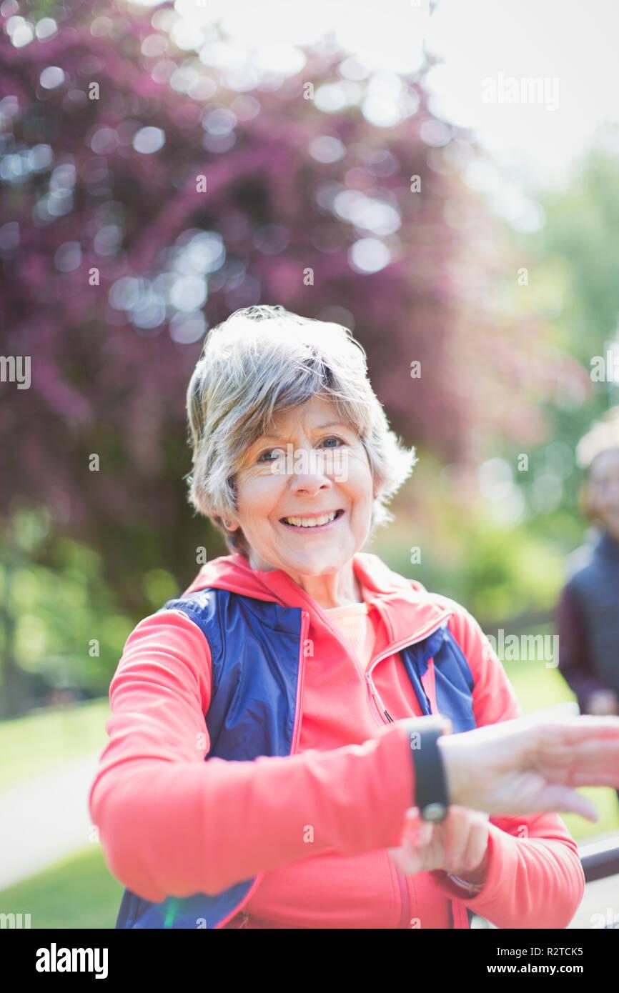 Portrait souriant, confiant active senior woman contrôle smart watch in park Photo Stock