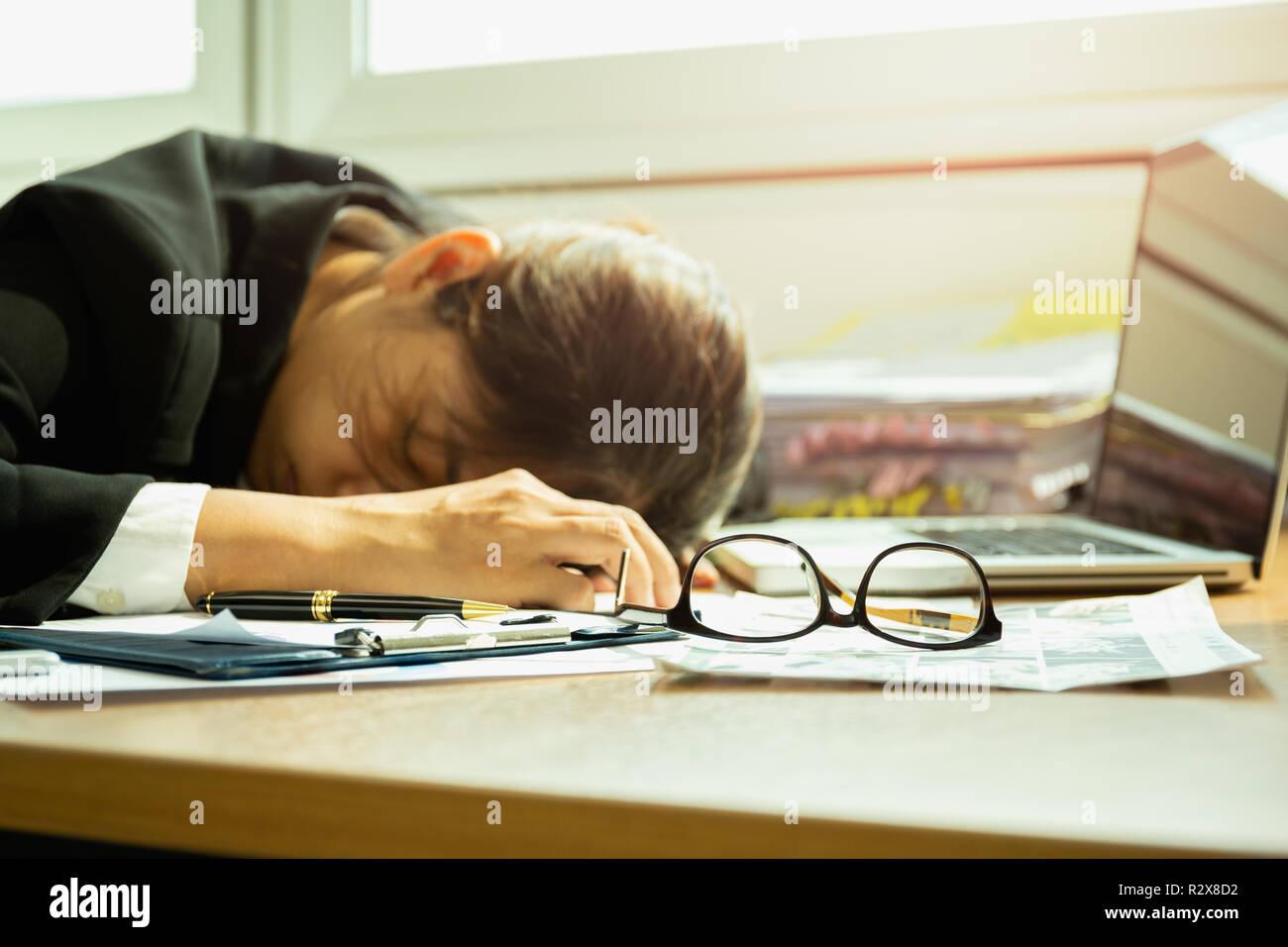 Businesswoman dormir au bureau sur des verres de mise au point