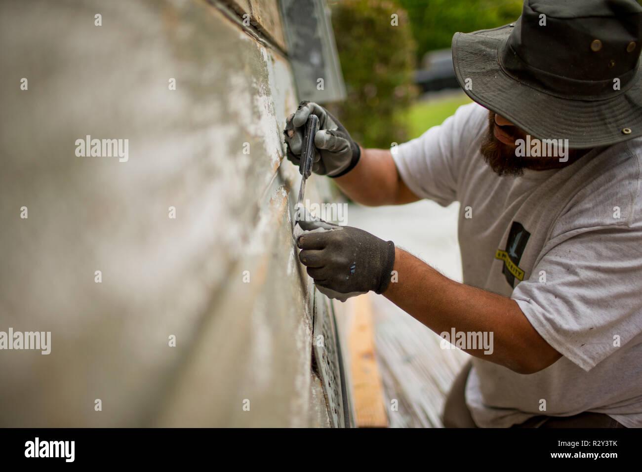 Le raclage des travailleurs d'une peinture old weathered chambre. Banque D'Images