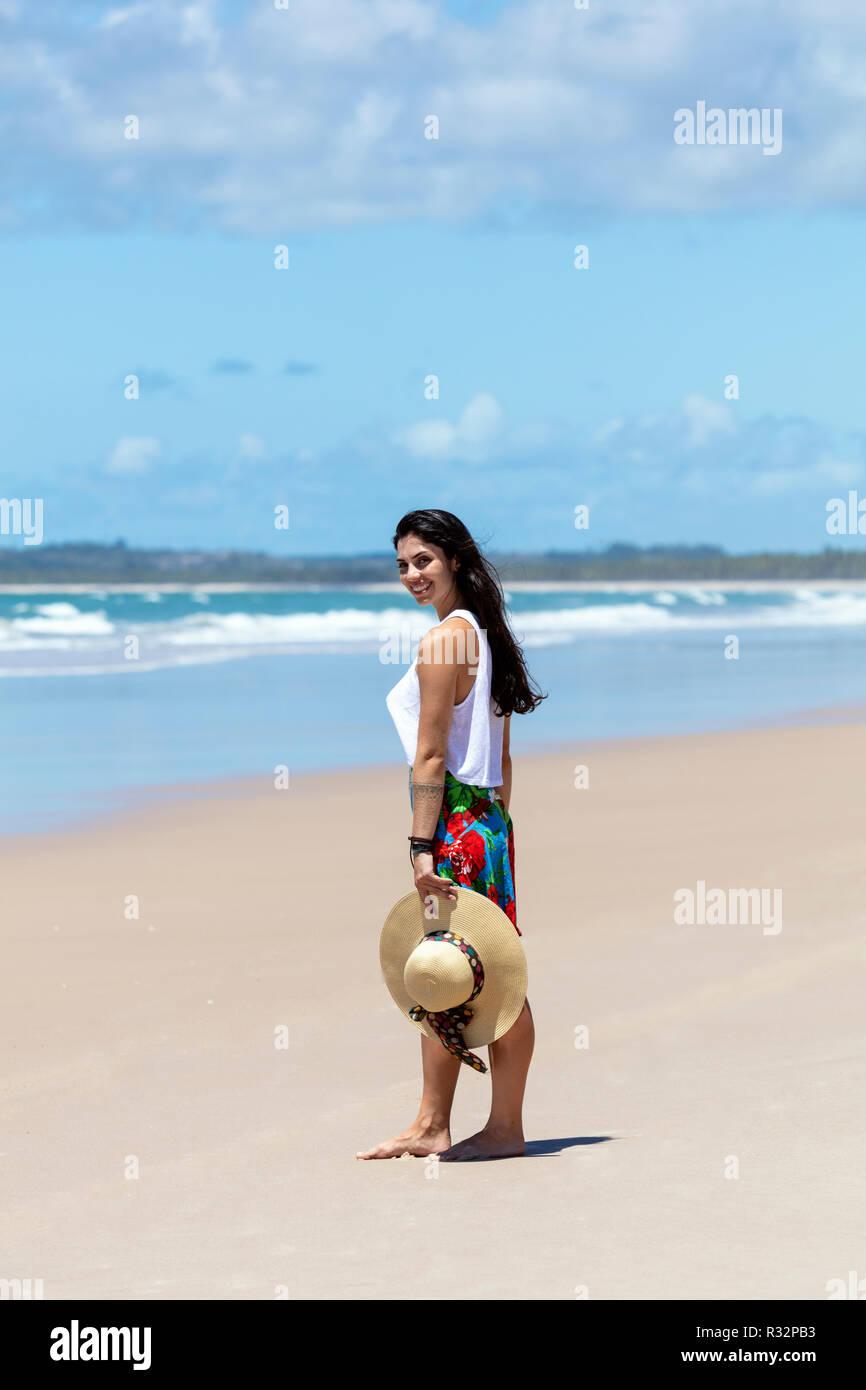 Une belle jeune femme dans une jupe, haut blanc et chapeau de paille sur une plage de sable blanc, palmier dans les tropiques Banque D'Images