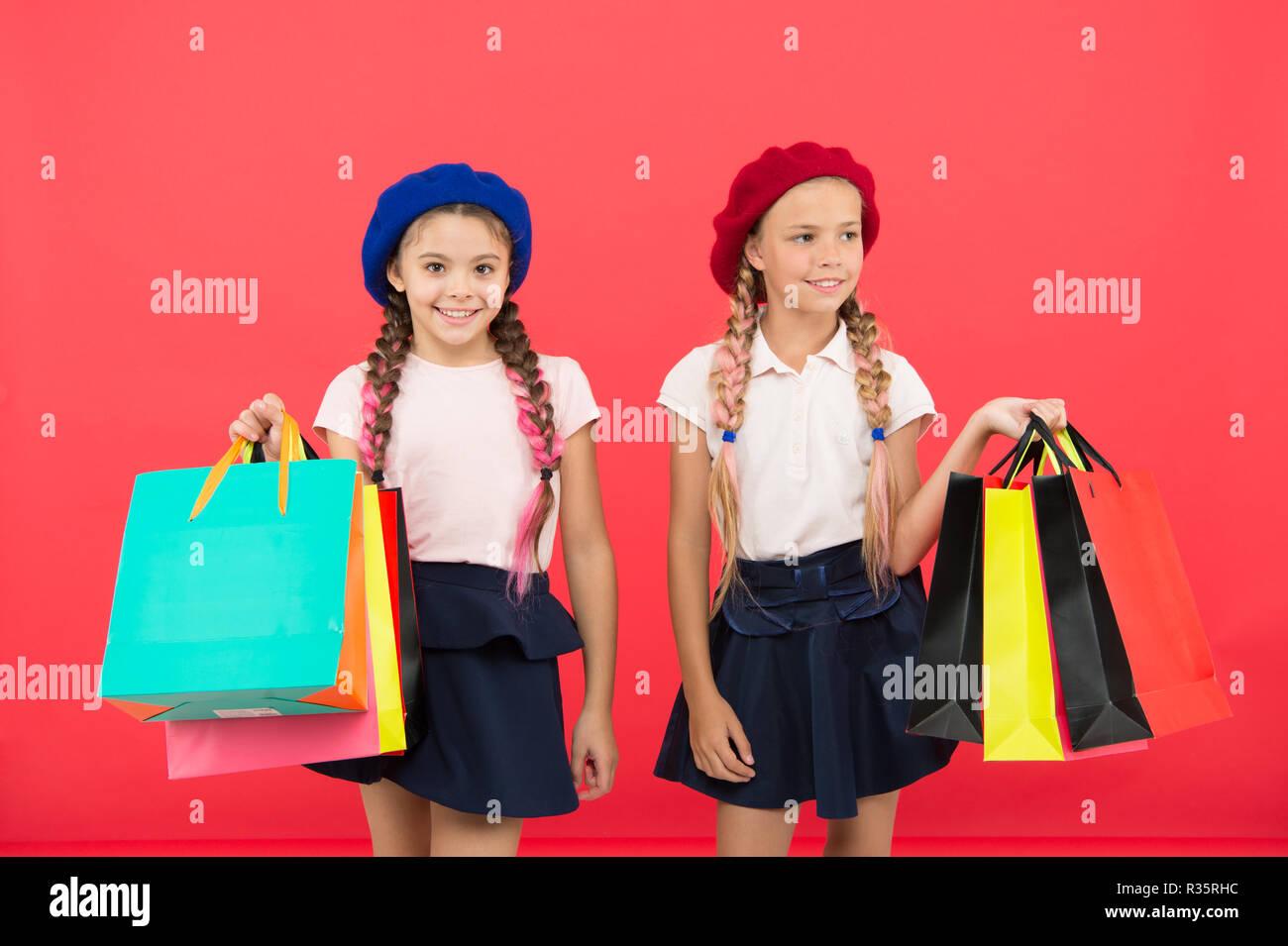 Les enfants élèves satisfaits par votre fond rouge. Obsédé par le shopping centres commerciaux et de l'habillement. Accro du concept. Signes que vous êtes accro au shopping. Enfants cute écolières tenir bunch sacs. Photo Stock