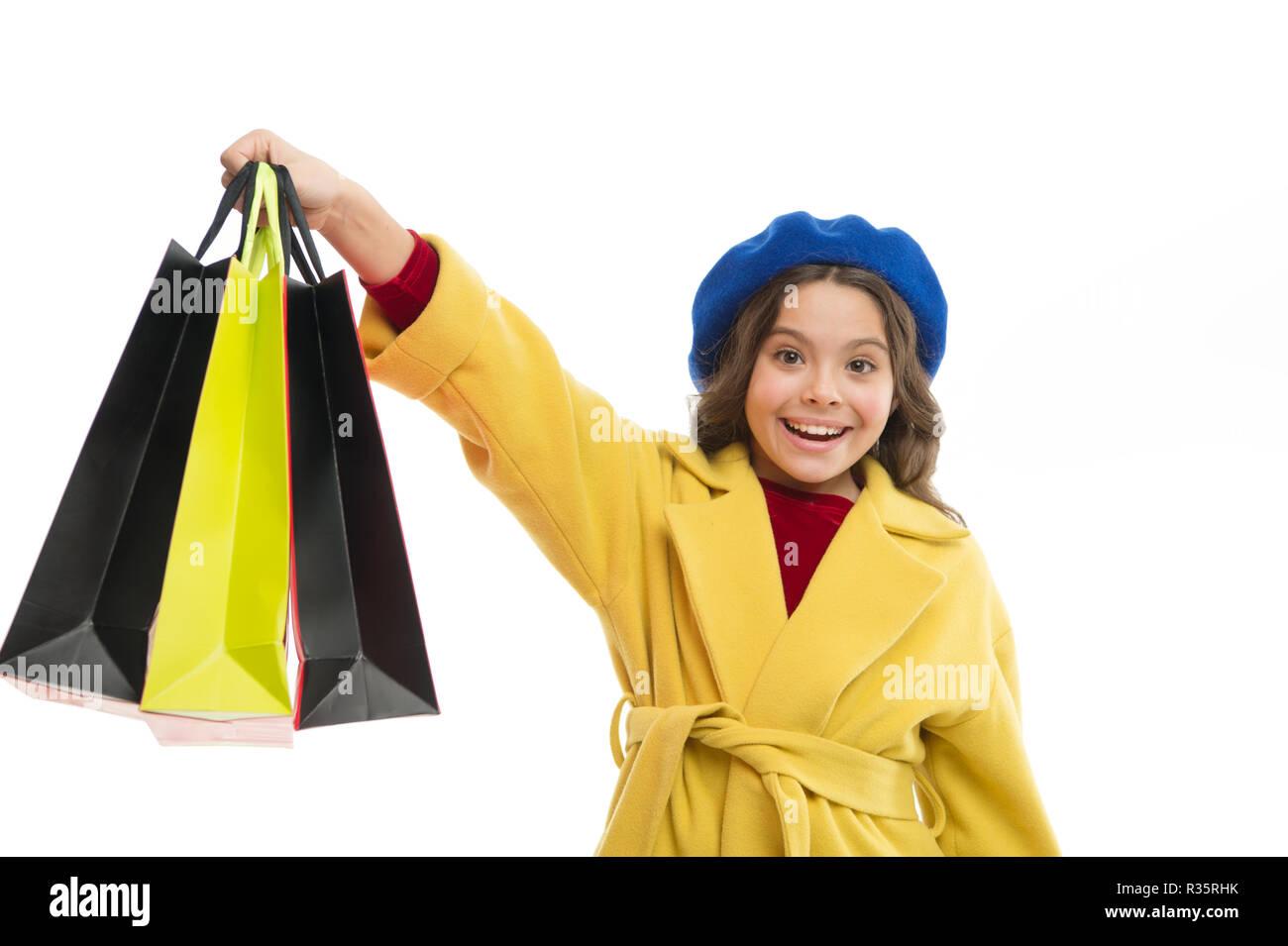 Satisfait par votre enfant isolé sur fond blanc. Obsédé par le shopping centres commerciaux et de l'habillement. Accro du concept. Signes que vous êtes accro au shopping. Kid cute little girl tenir bunch sacs. Photo Stock