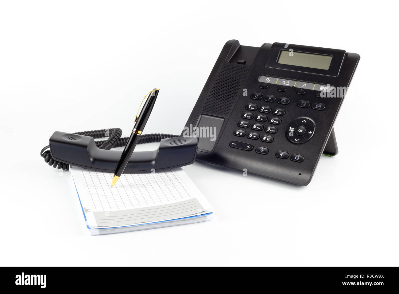 IP noir -téléphone, ordinateur portable et stylo pour écrire sur un fond blanc. Concept de poste de travail Banque D'Images