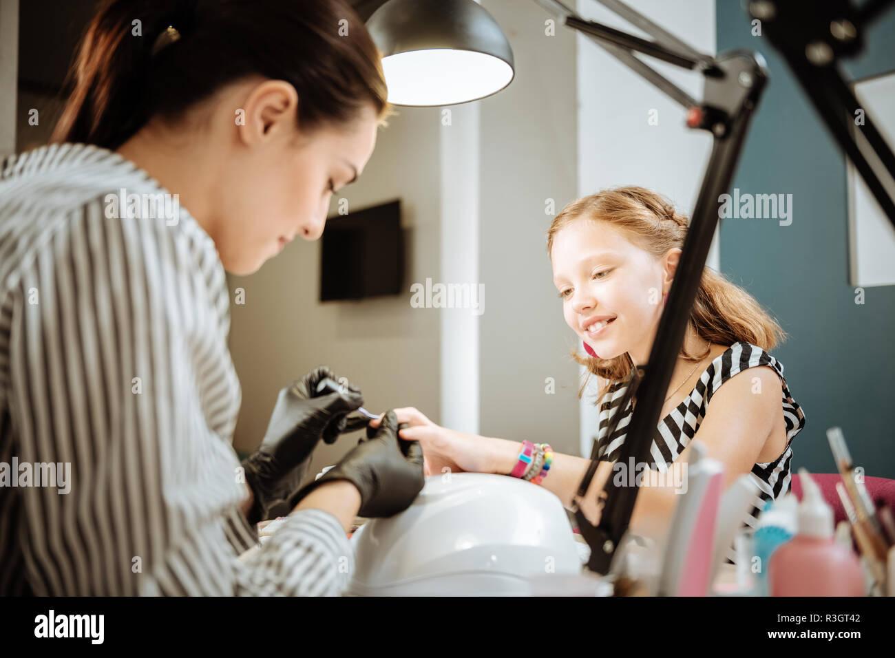 Mère travaillant comme artiste de l'ongle manucure pour son joli fille adolescente Banque D'Images