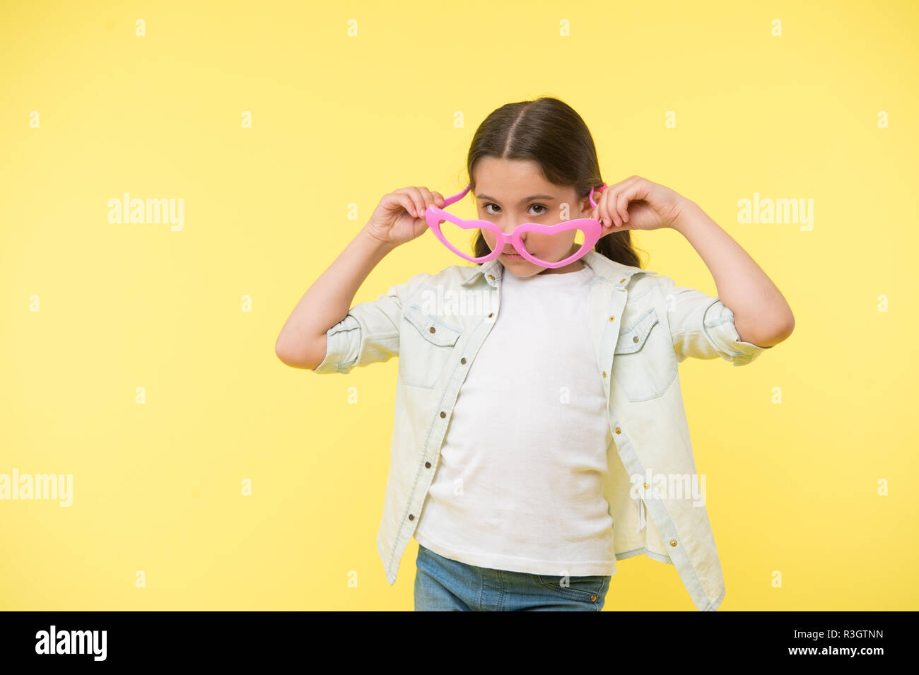 5891cb44df24f4 Fille look dans des verres en forme de coeur sur fond jaune. Petit enfant  avec accessoire de mode. Restez calme et porter des lunettes cool.