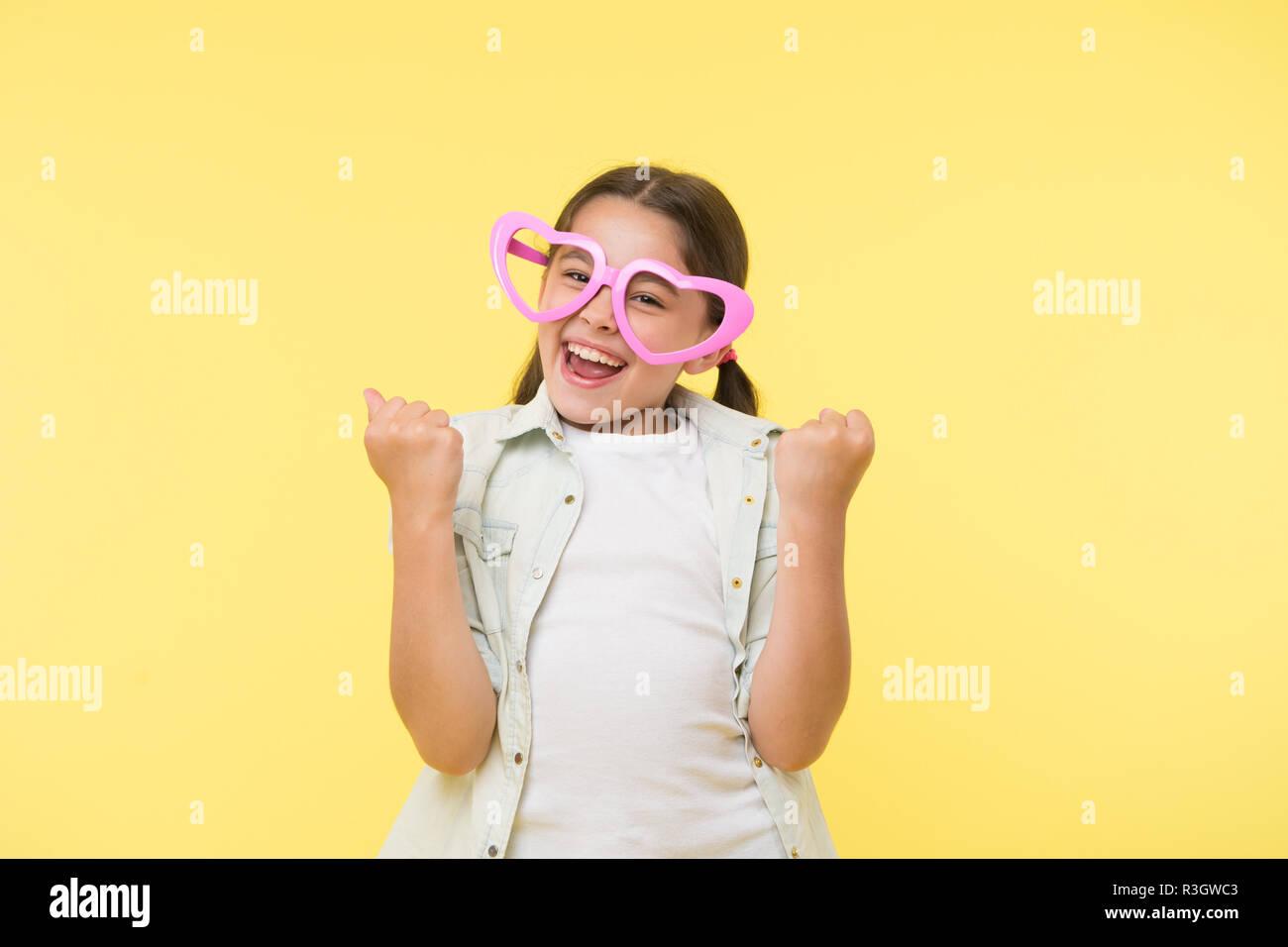 194f9b337ea783 Heureux l enfant porter des lunettes en forme de coeur sur fond jaune.  Petite