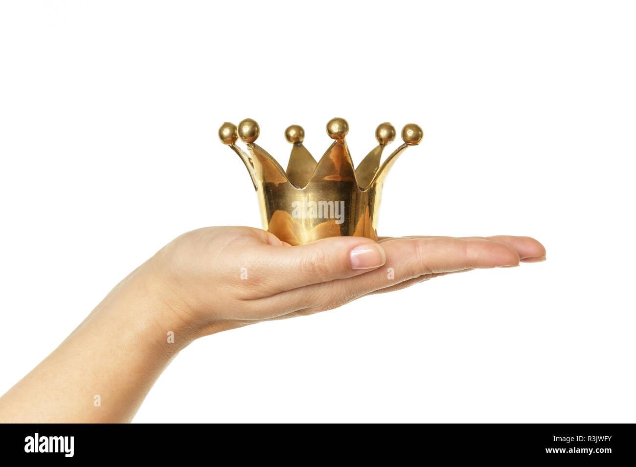 Femme hand holding golden crown isolé sur fond blanc. Concept pour le succès. Photo Stock