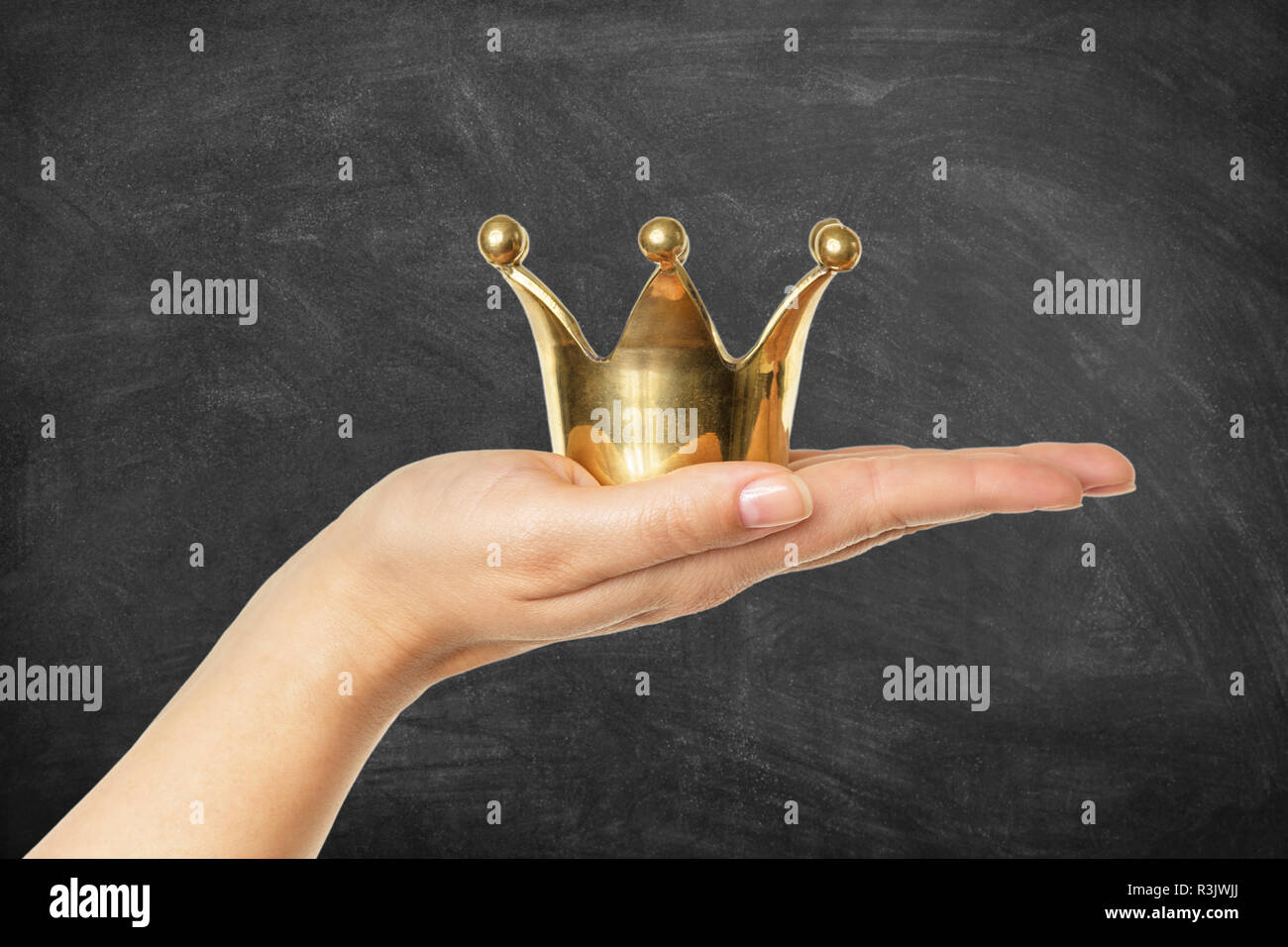Femme main tenant couronne d'or en face d'un tableau arrière-plan. Concept pour le succès. Photo Stock