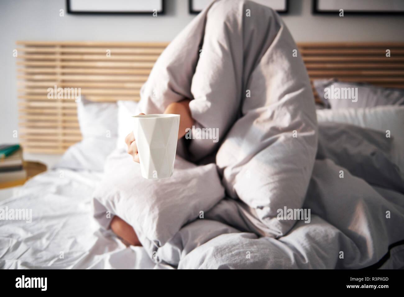 Femme cachée sous couverture café exigeants Banque D'Images