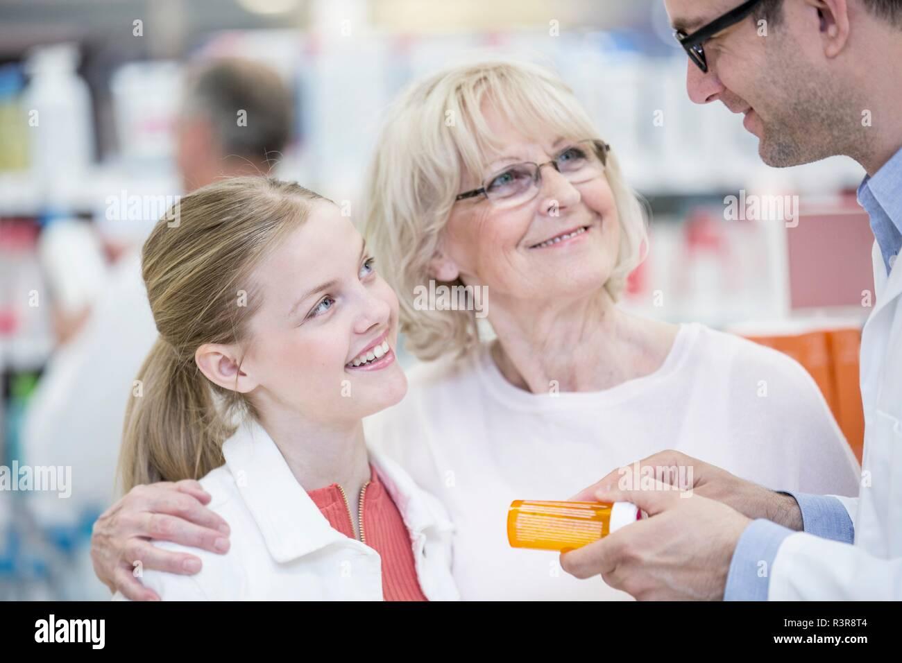 Homme pharmacien expliquant ces médicaments à mature woman and girl en pharmacie. Photo Stock