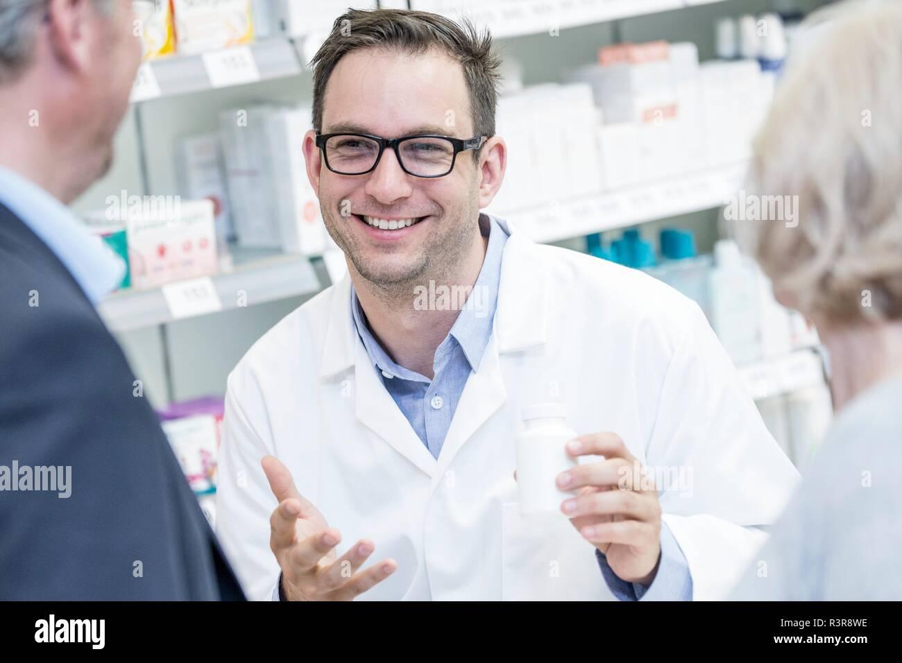 Male pharmacien expliquant ces médicaments à des clients dans nos pharmacies. Photo Stock