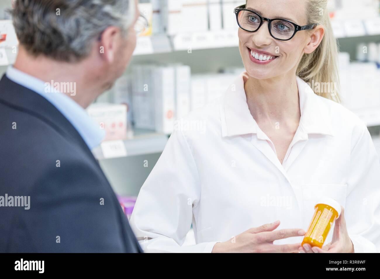 Smiling female pharmacist expliquant aux clients de médicaments en pharmacie. Photo Stock
