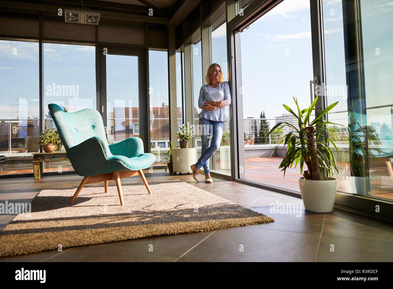 Mature Woman standing à la fenêtre à la maison à out Banque D'Images