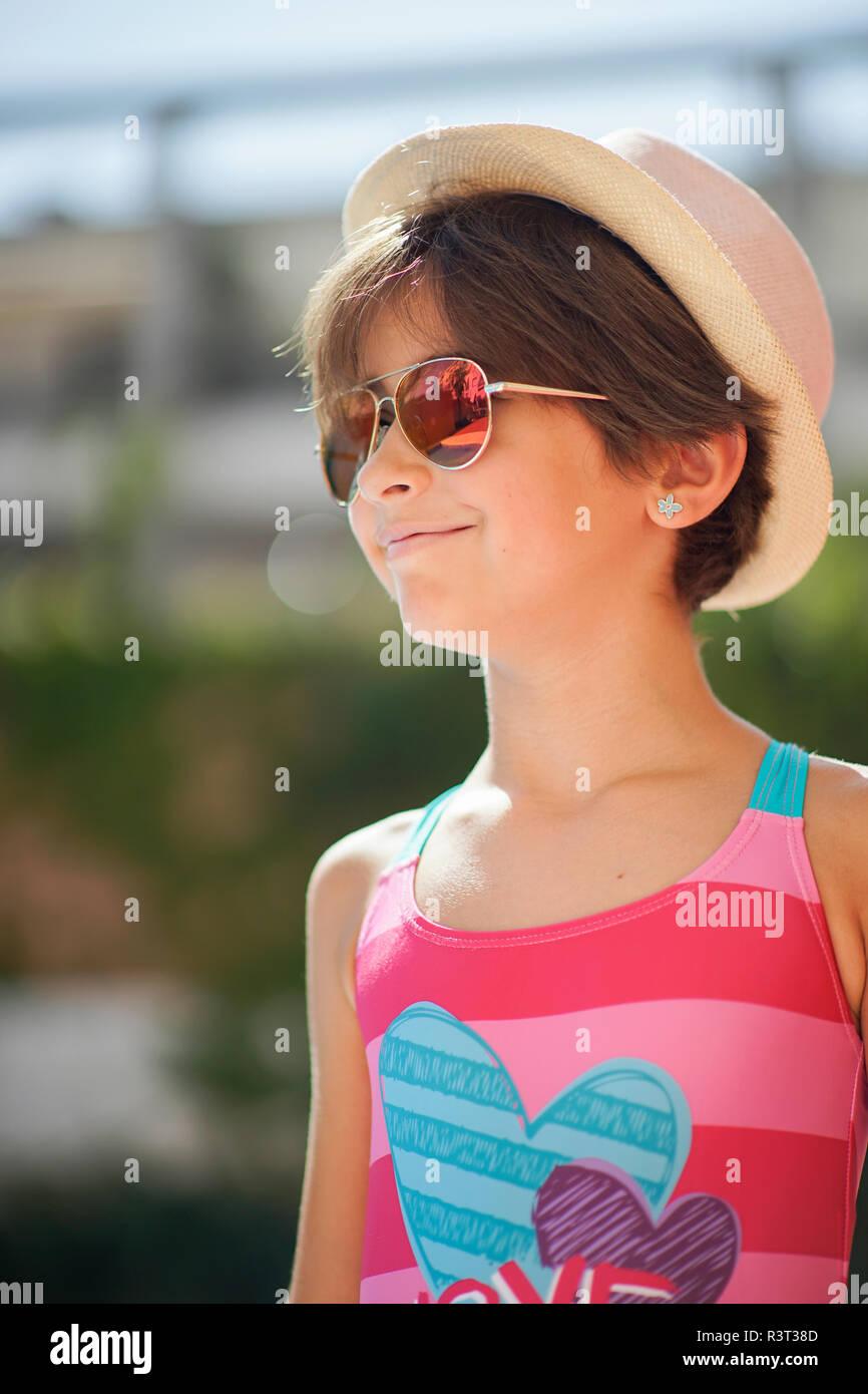 Portrait de jeune fille avec des lunettes de soleil et chapeau, à côté Banque D'Images