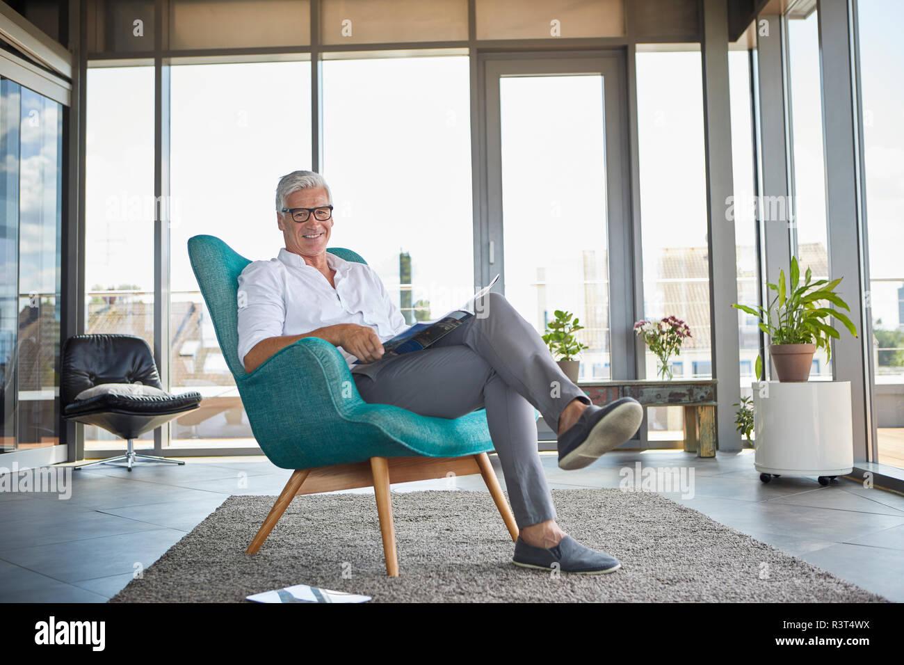 Portrait of smiling mature man avec une brochure de vous détendre dans un fauteuil près de la fenêtre à la maison Photo Stock